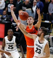 Colorado forward Lucas Siewert, front, battles for control of a rebound with Oregon State forward Tres Tinkle, center, as Colorado guard McKinley Wright IV looks on in the first half of an NCAA college basketball game Thursday, Jan. 31, 2019, in Boulder, Colo.
