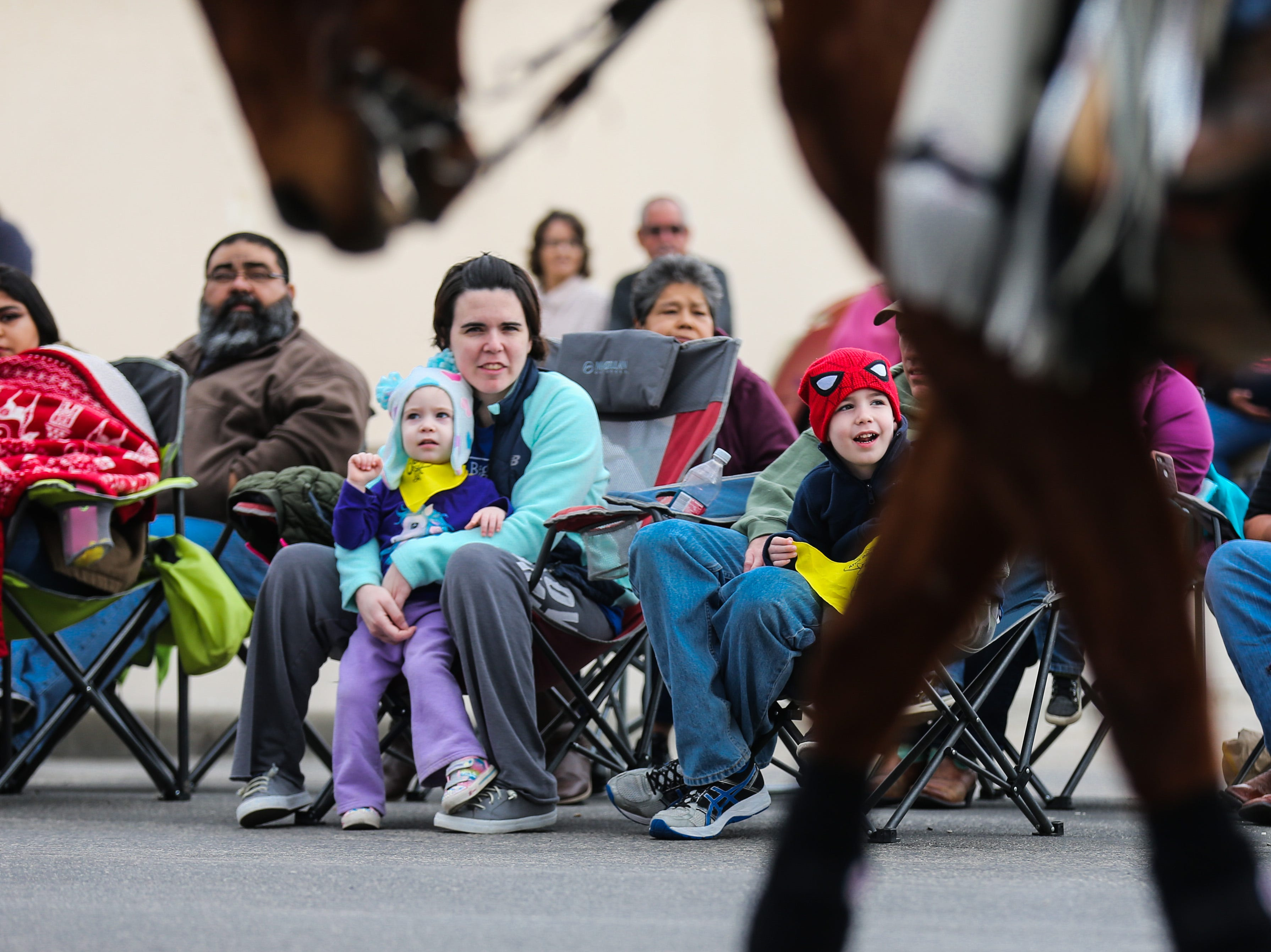 Spectators bundle up as participants make their way down the street during the San Angelo Stock Show and Rodeo Parade to start Saturday, Feb. 2, 2019, in downtown San Angelo.