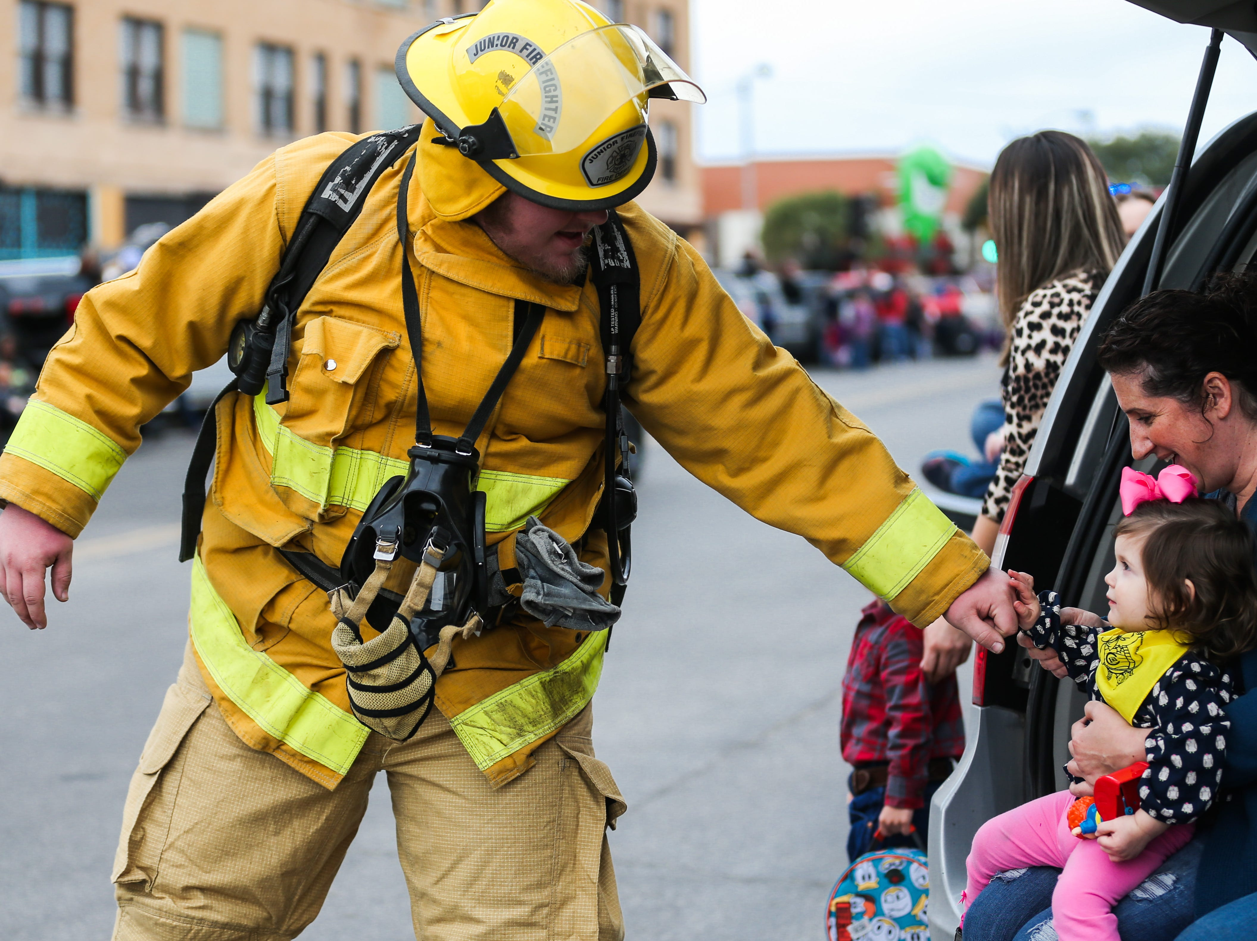 A firefighters greets Malena Gore, 18 months, as he makes his way down the street with the San Angelo Stock Show and Rodeo Parade to start Saturday, Feb. 2, 2019, in downtown San Angelo.