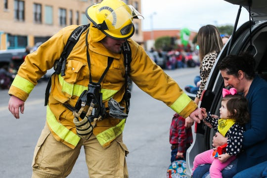 A firefighters greets Malena Gore, 18 months, as he makes his way down the street with the San Angelo Stock Show & Rodeo Parade to start Saturday, Feb. 2, 2019, in downtown San Angelo.