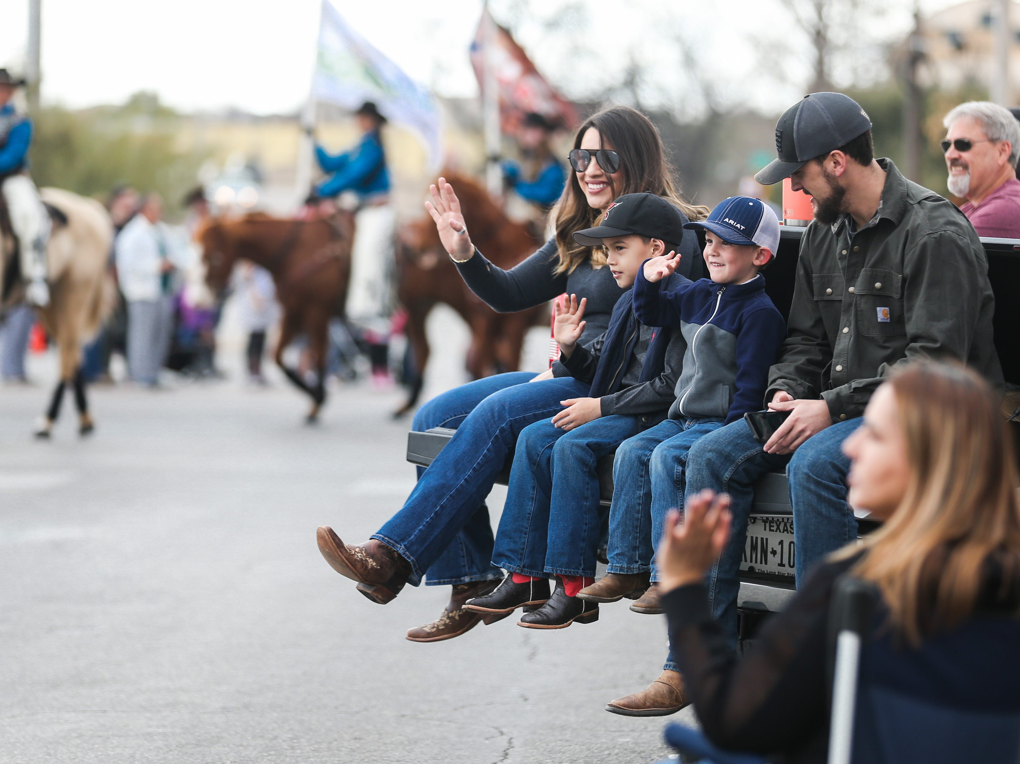 Spectators wave to participants during the San Angelo Stock Show and Rodeo Parade to start Saturday, Feb. 2, 2019, in downtown San Angelo.