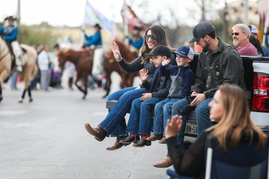 Spectators wave to participants during the San Angelo Stock Show & Rodeo Parade to start Saturday, Feb. 2, 2019, in downtown San Angelo.