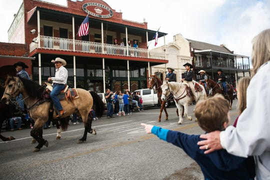 Spectators watch as horsemen twirl their ropes while riding during the San Angelo Stock Show and Rodeo Parade to start Saturday, Feb. 2, 2019, in downtown San Angelo.