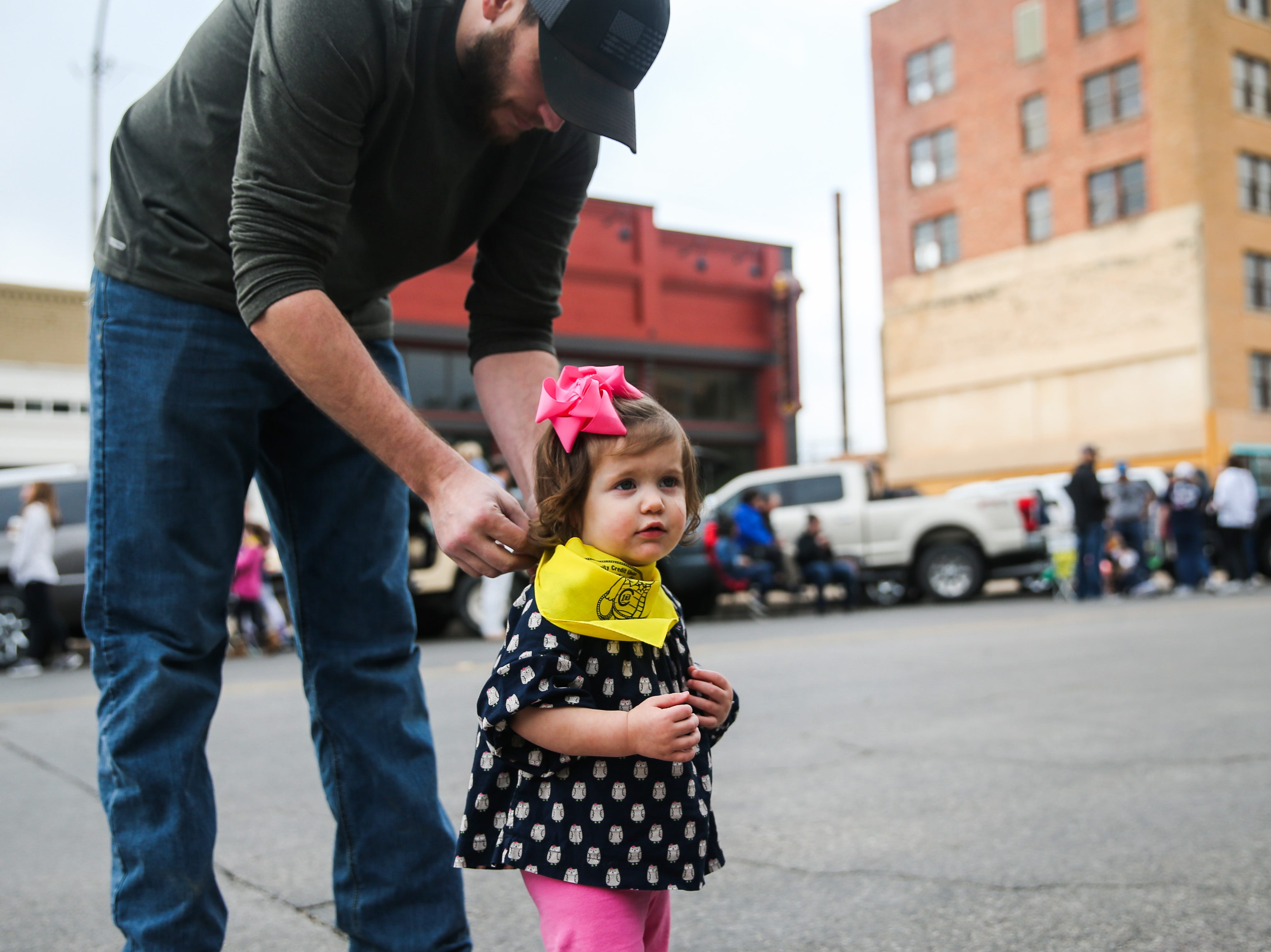 Dustin Gore puts a bandana on Malena Gore, 18 months, before the San Angelo Stock Show and Rodeo Parade to start Saturday, Feb. 2, 2019, in downtown San Angelo.
