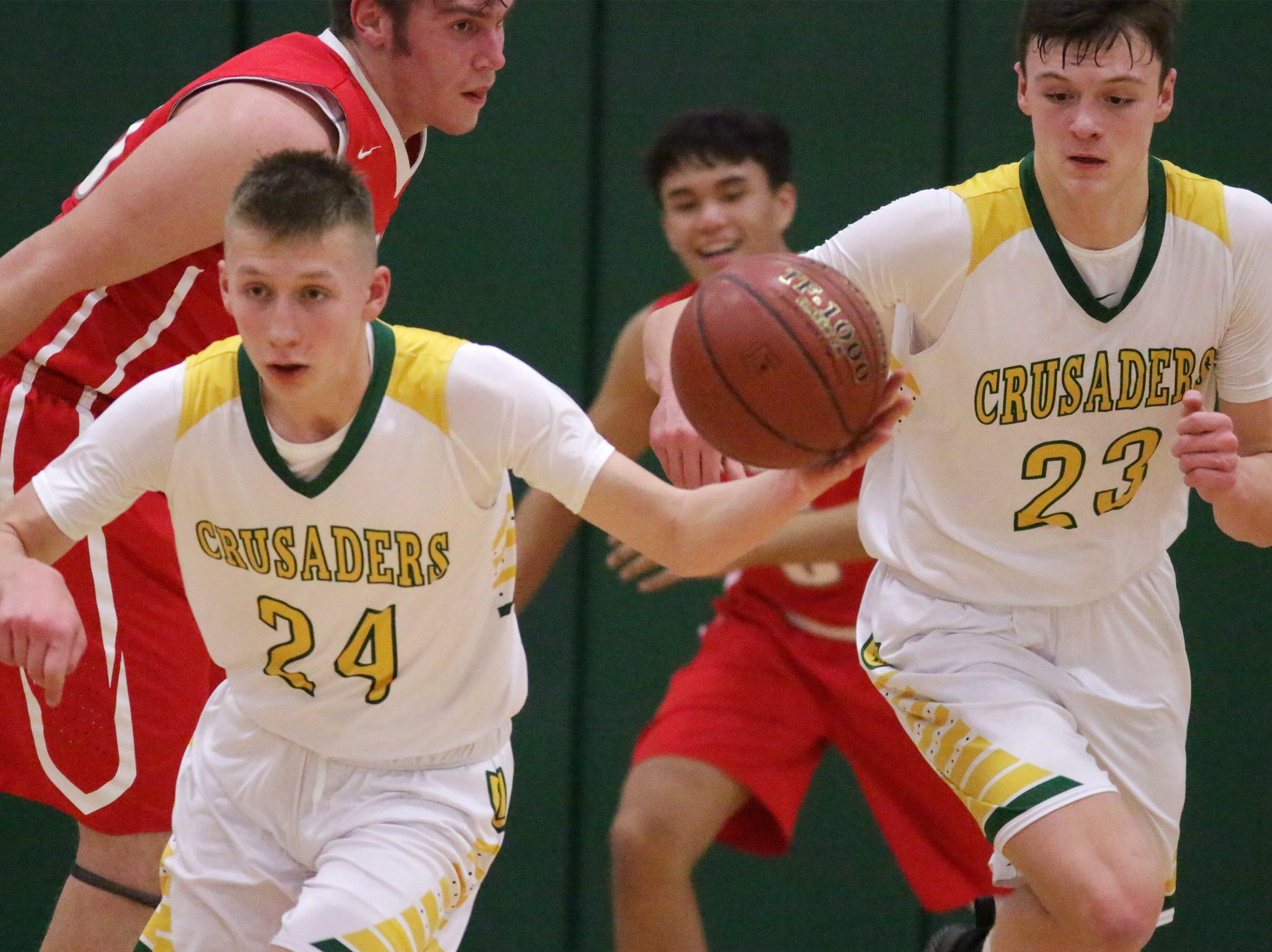 Sheboygan Lutheran's Casey Verghagen (24) drives the ball by Jacob Ognacevic (23) during their win against Manitowoc Lutheran, Friday, February 1, 2019, in Sheboygan, Wis.