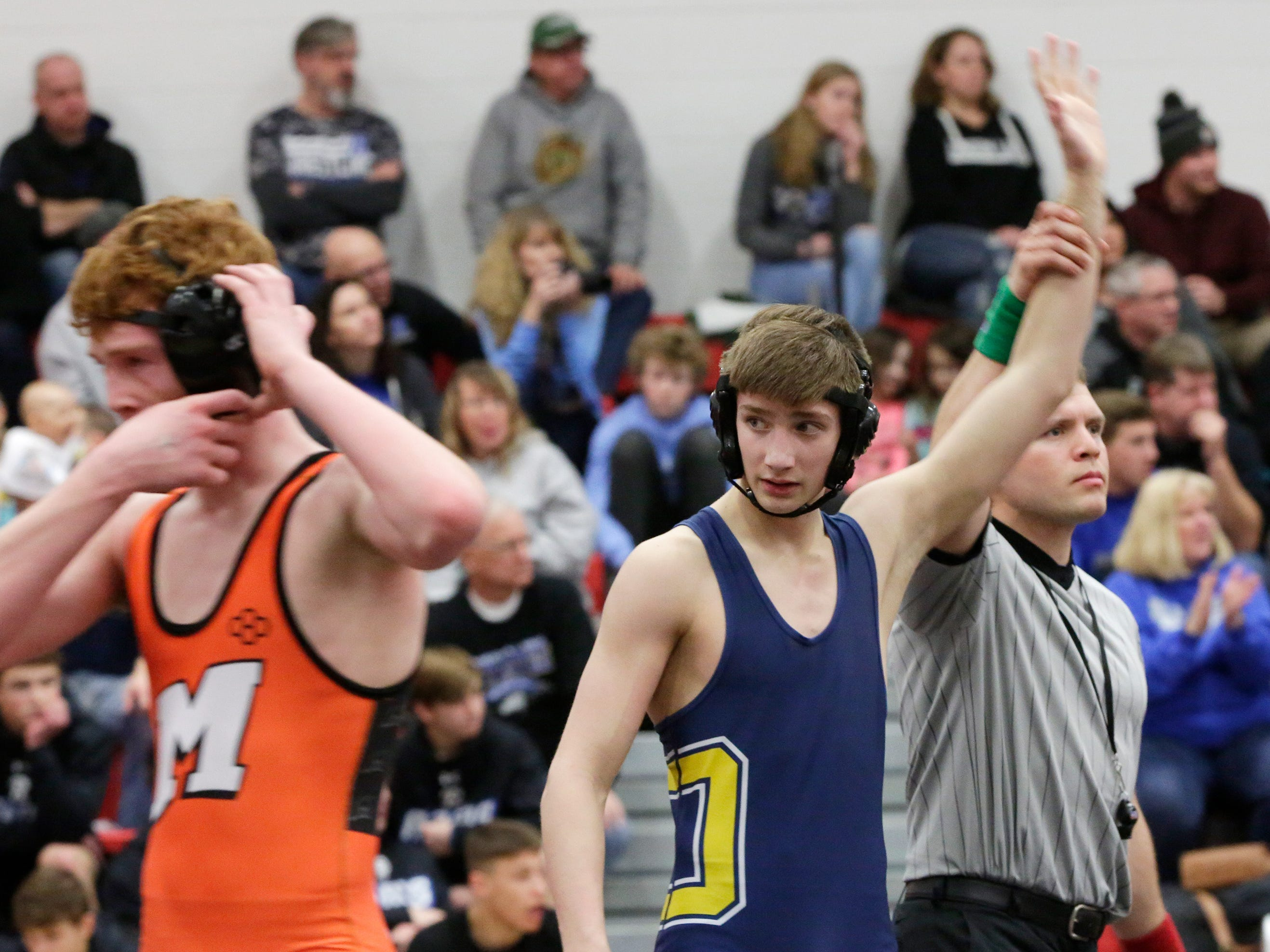 Ozaukee's Travis Simpson, right, looks to the crowd after winning a 132-pound match with Mishicot's Brant Cracraft, Saturday, February 2, 2019, in Oostburg, Wis.