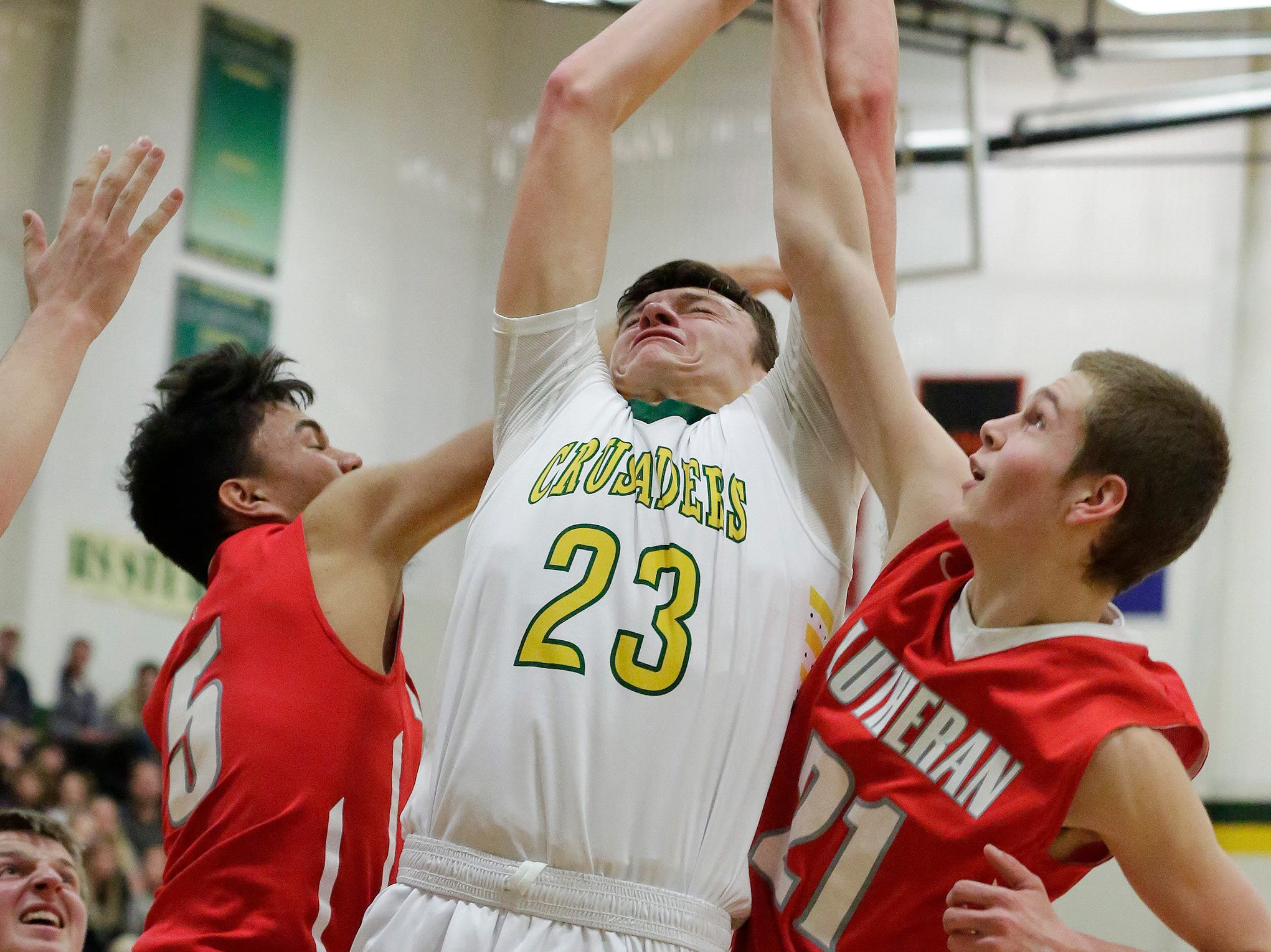 Sheboygan Lutheran's Jacob Ognacevic (23) is well guarded by Manitowoc Lutheran players while he attempts to shoot a shot, Friday, February 1, 2019, in Sheboygan, Wis.