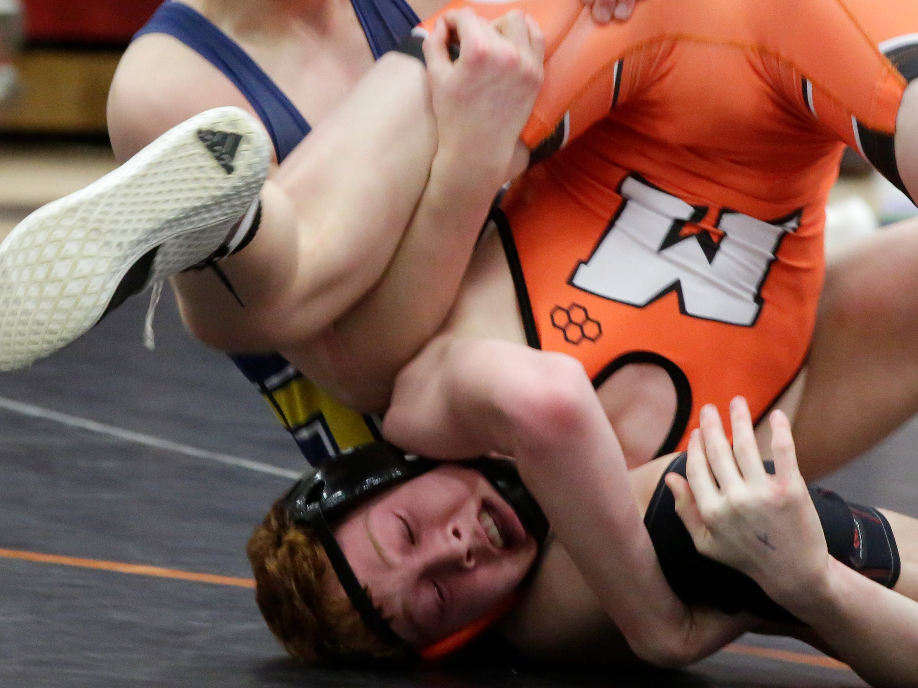 Ozaukee's Travis Simpson, top, wrestles Mishicot's Brant Cracraft in a 132-pound match, Saturday, February 2, 2019, in Oostburg, Wis.