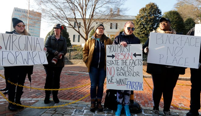 Demonstrators hold signs and chant outside the Governors Mansion at the Capitol in Richmond, Va., Saturday, Feb. 2, 2019. The demonstrators are calling for the resignation of Gov. Ralph Northam after a 30 year old photo of him on his medical school yearbook photo was widely distributed Friday.