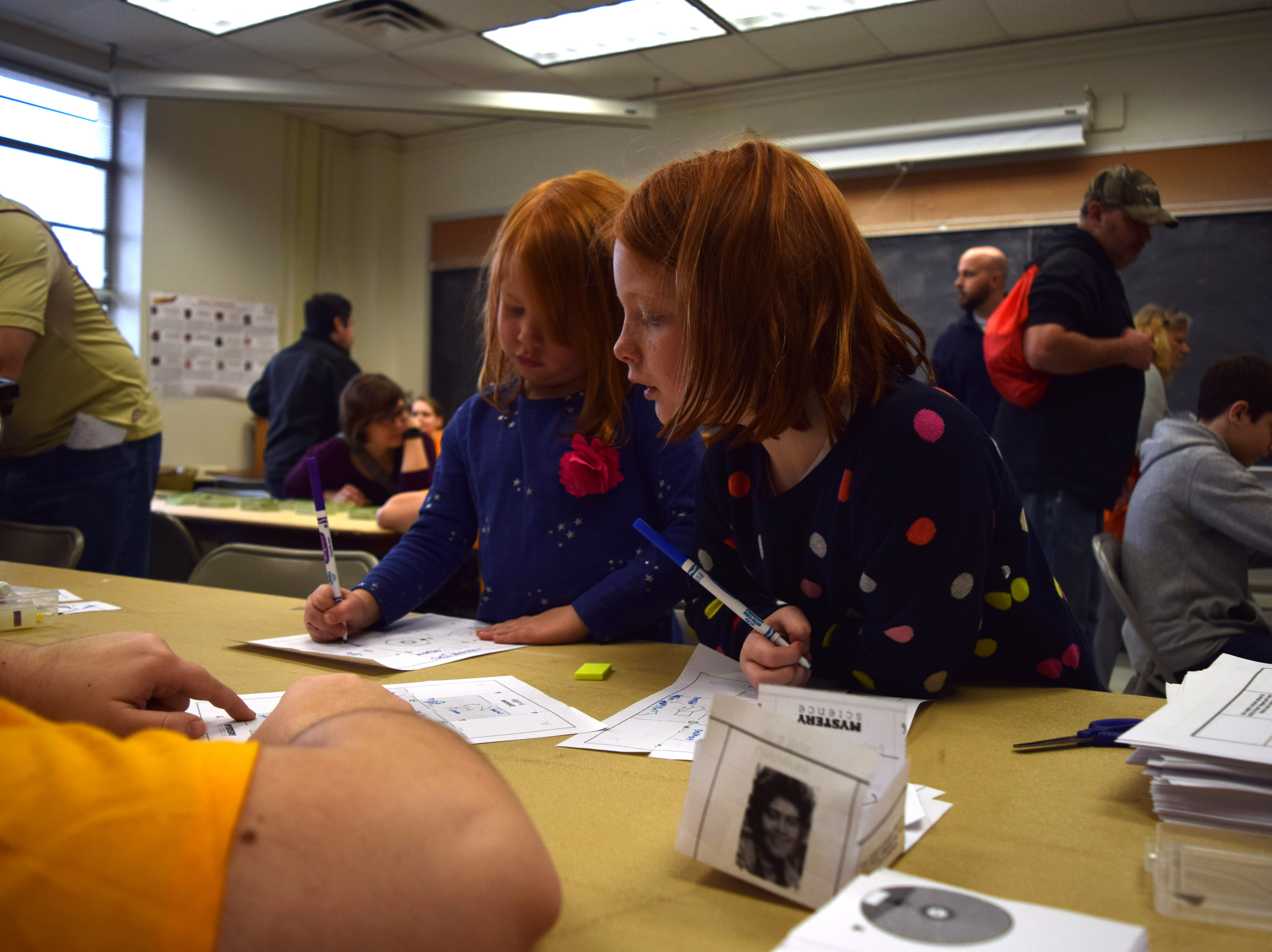 Fiona King (left) and Ellery King (right) learn about constellations in the Women in Mathematics room during FSU Math Fun Day on Saturday.