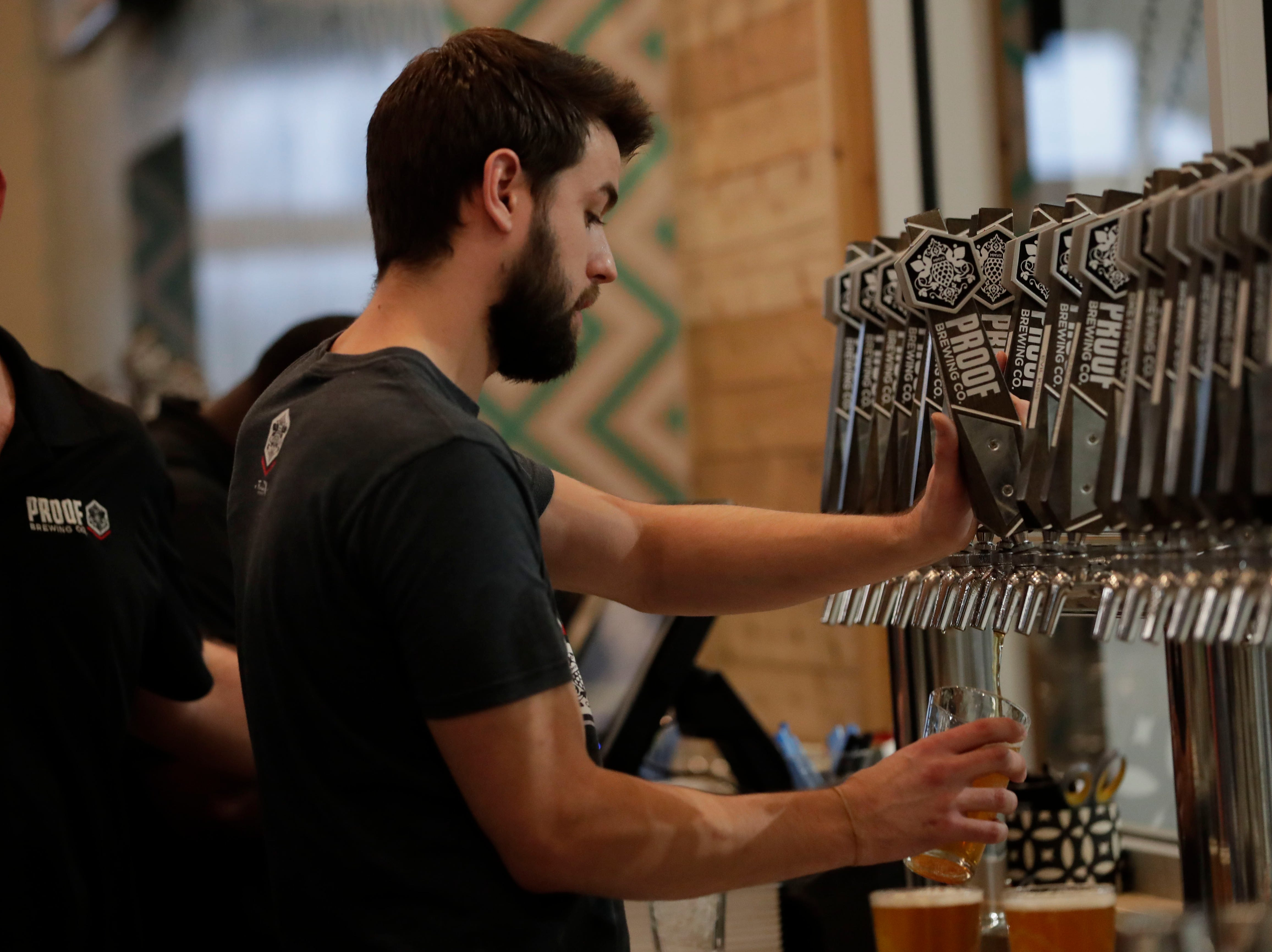 Kris Links, a bartender at Proof Brewery, pours drinks for customers during the soft opening of the new Proof Brewery, Friday, Feb. 1, 2019.