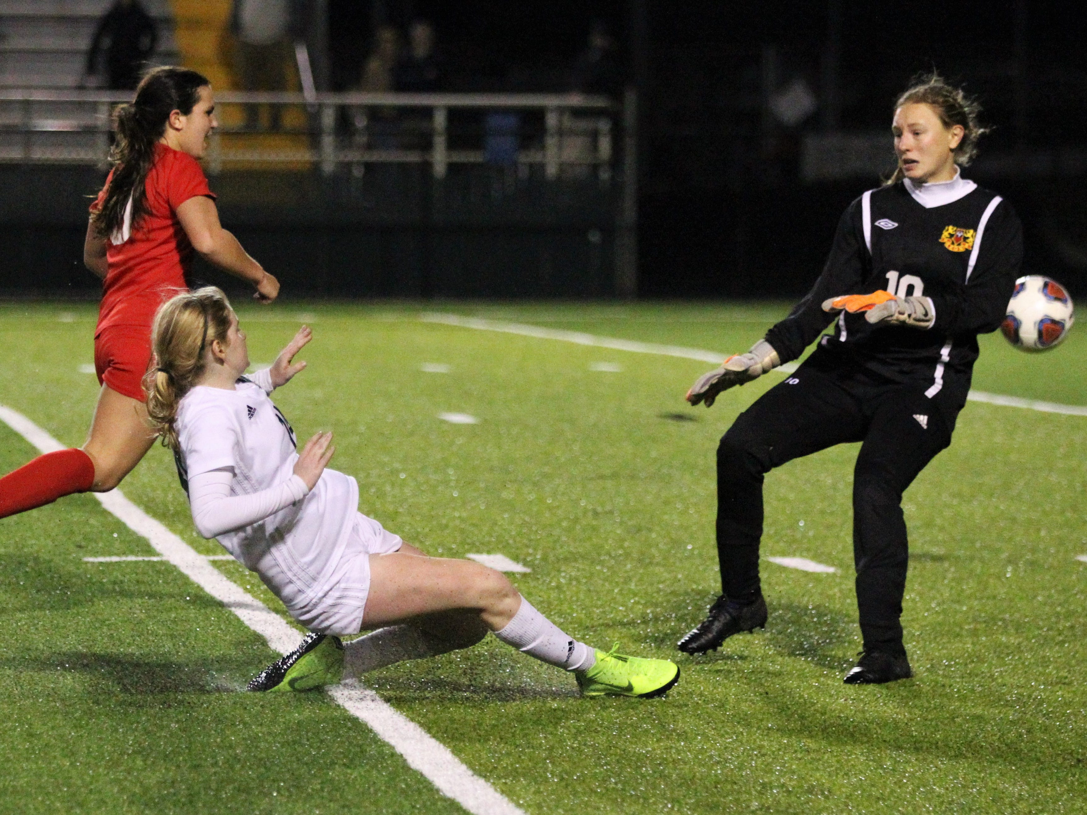 Leon keeper Regan Hermeling comes out of the box to disrupt a last-second shot attempt by Lincoln senior McIver Levy as Leon's girls soccer team beat Lincoln 2-1 in the District 2-4A championship at Gene Cox Stadium on Feb. 1, 2019.