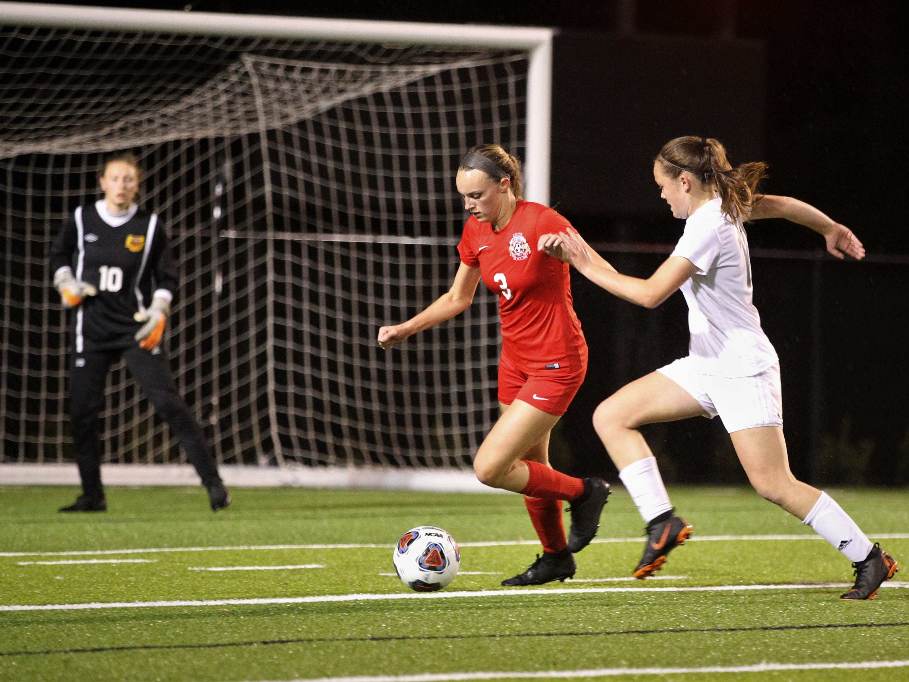 Leon defender Madison Rumenik tries to dribble clear of Lincoln's Meredith Camron in the box as Leon's girls soccer team beat Lincoln in the District 2-4A championship on Feb. 1, 2019.