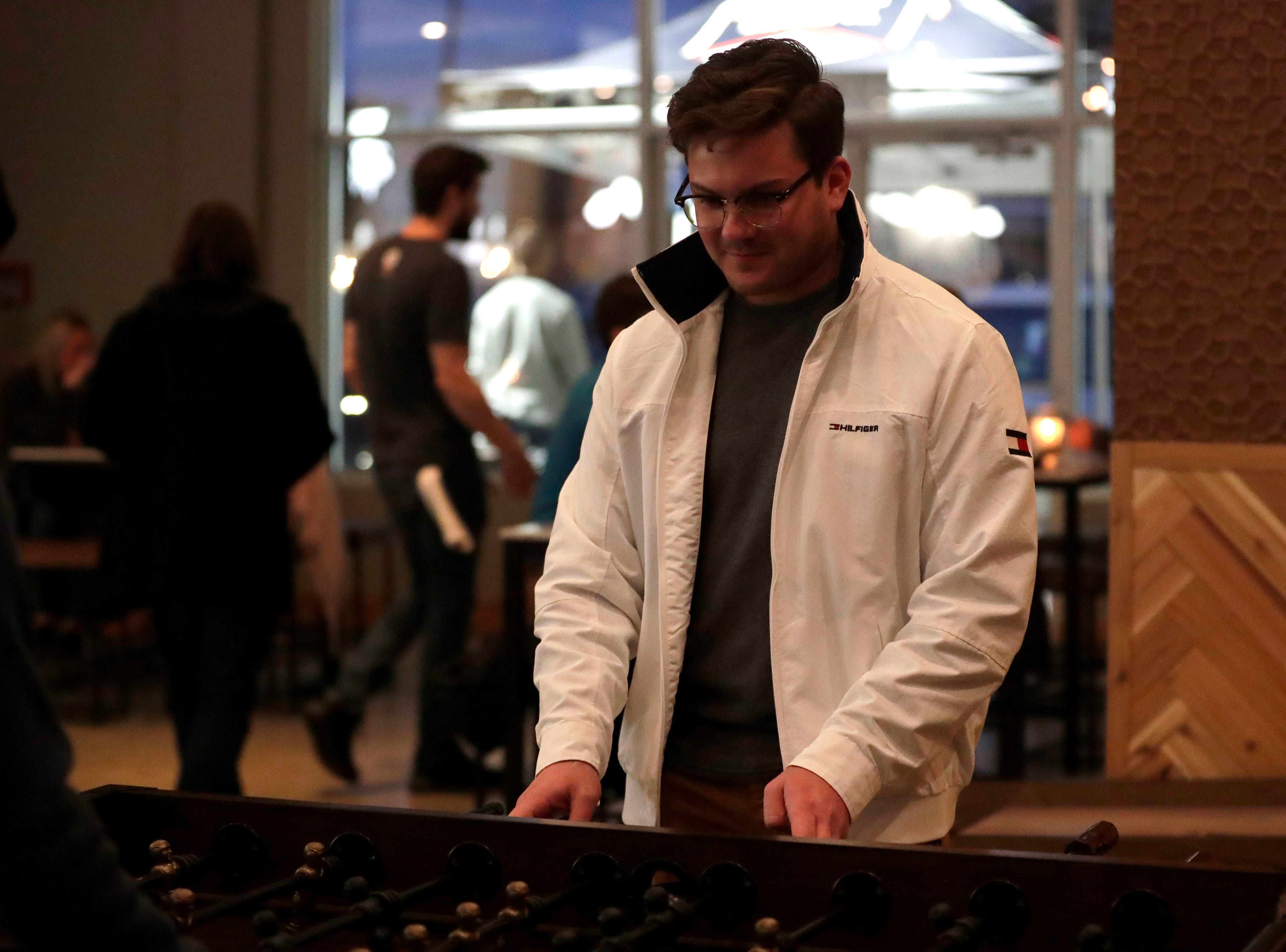 Tyler French challenges his friend to a round of foosball at the soft opening of the new Proof Brewery, Friday, Feb. 1, 2019.