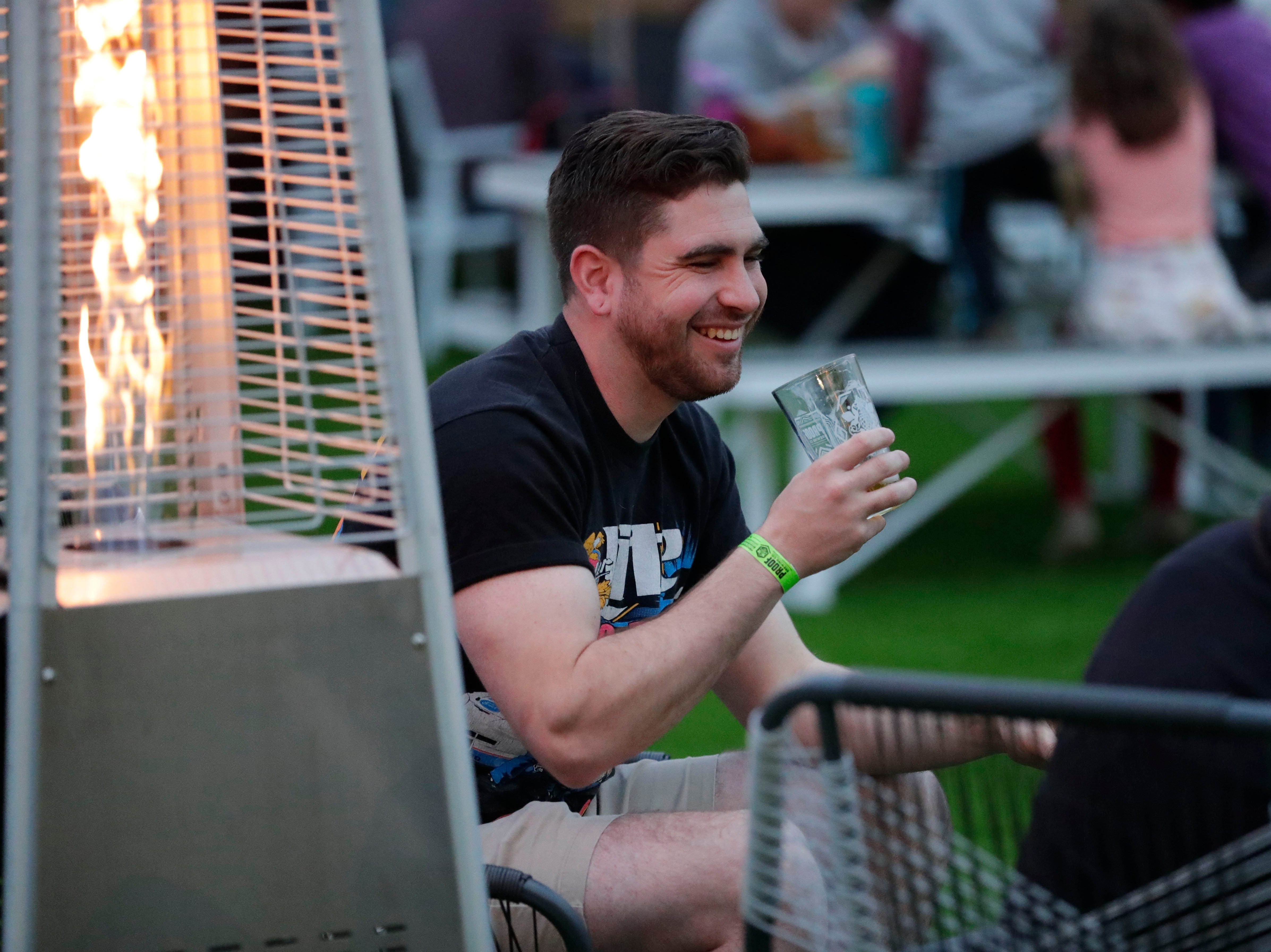 Irvine Leonard laughs while chatting with friends and enjoying his beer in the outdoor area of the new Proof Brewery during the brewery's soft opening, Friday, Feb. 1, 2019.