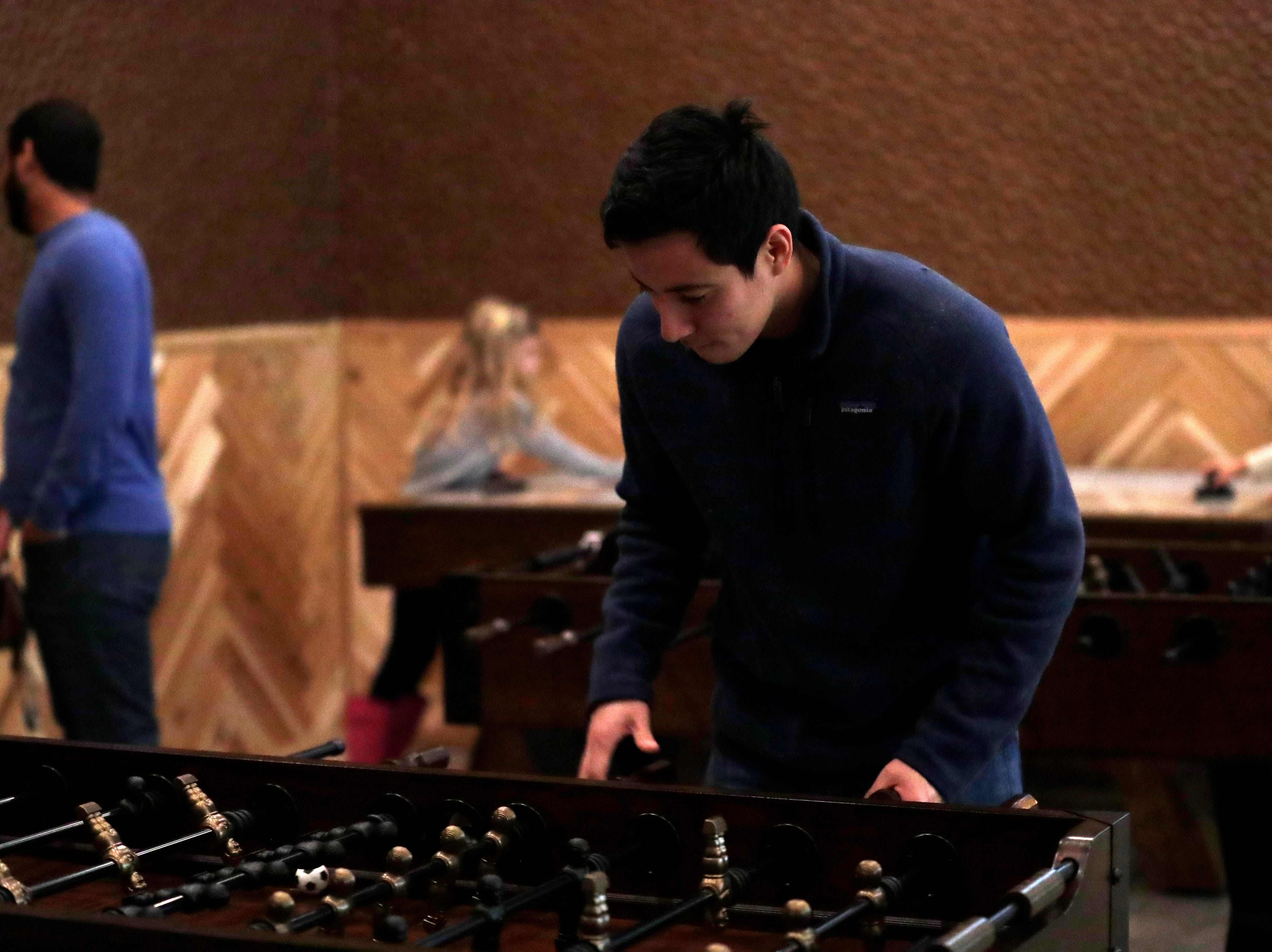 Fernando Quiroz plays his friend in foosball at the soft opening of the new Proof Brewery, Friday, Feb. 1, 2019.
