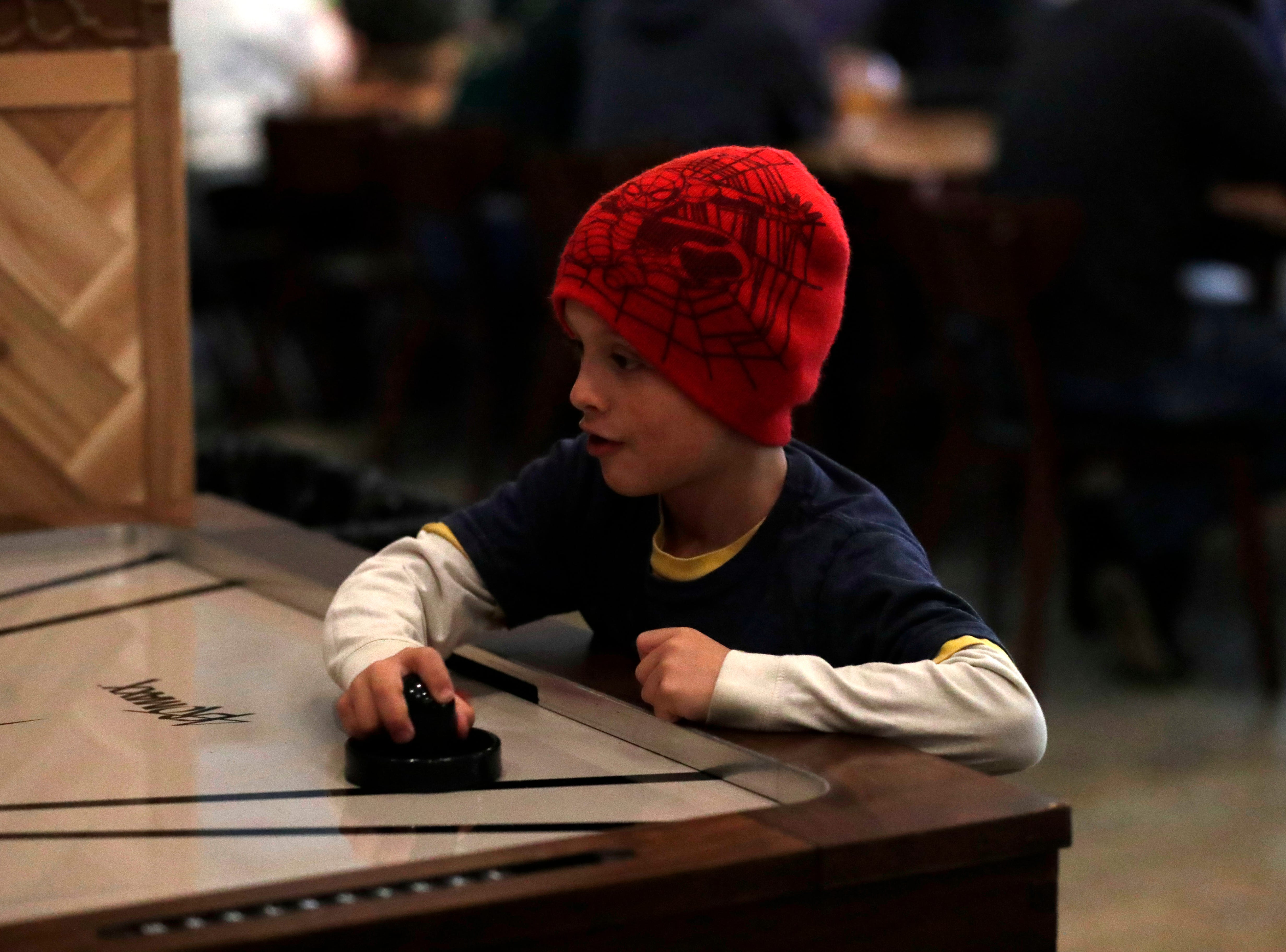 Marino Corradi, 7, plays air hockey at the soft opening of the new Proof Brewery, Friday, Feb. 1, 2019.