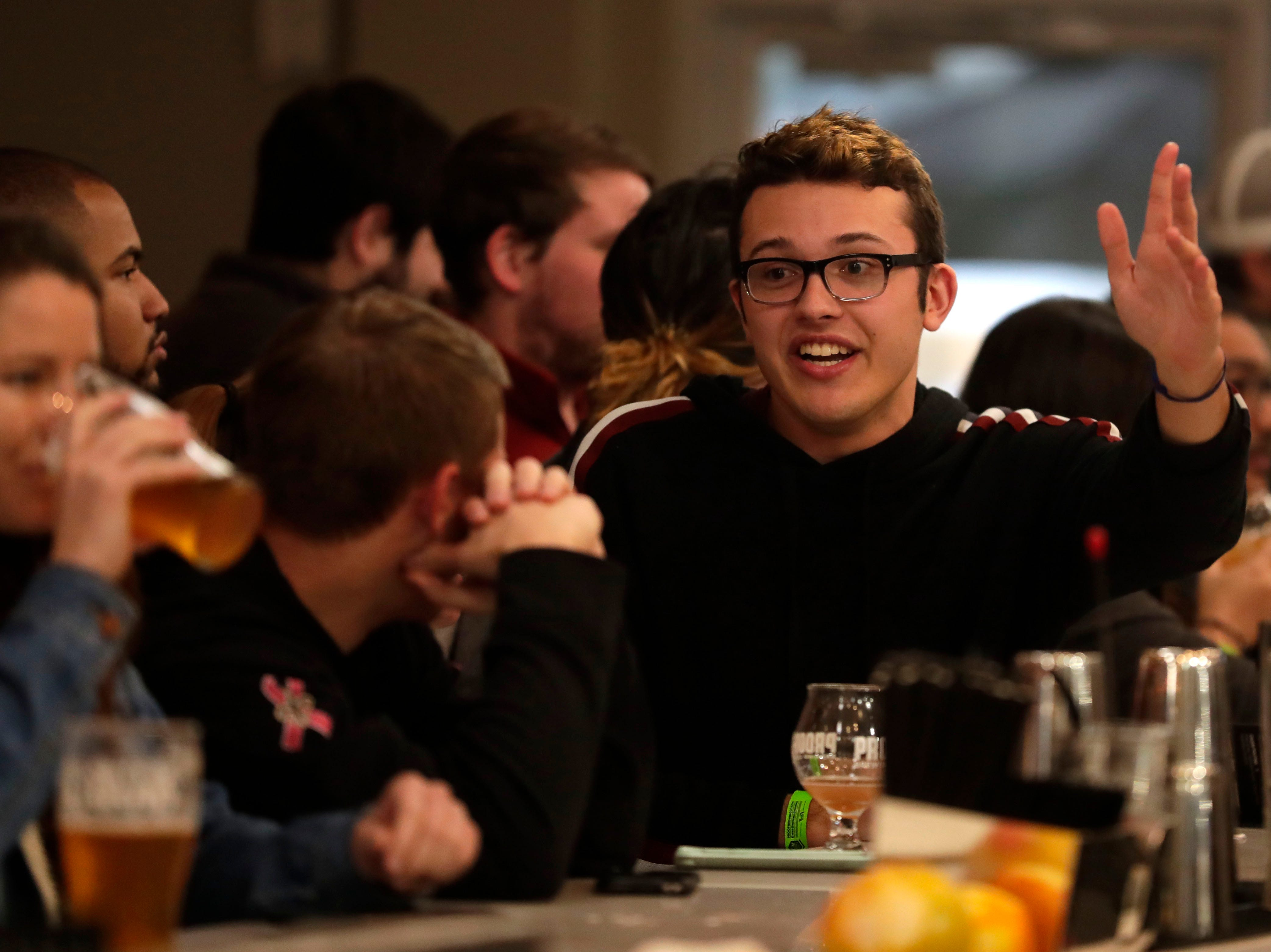 A young man talks with his friends while enjoying drinks at the bar of the new Proof Brewery during their soft opening, Friday, Feb. 1, 2019.