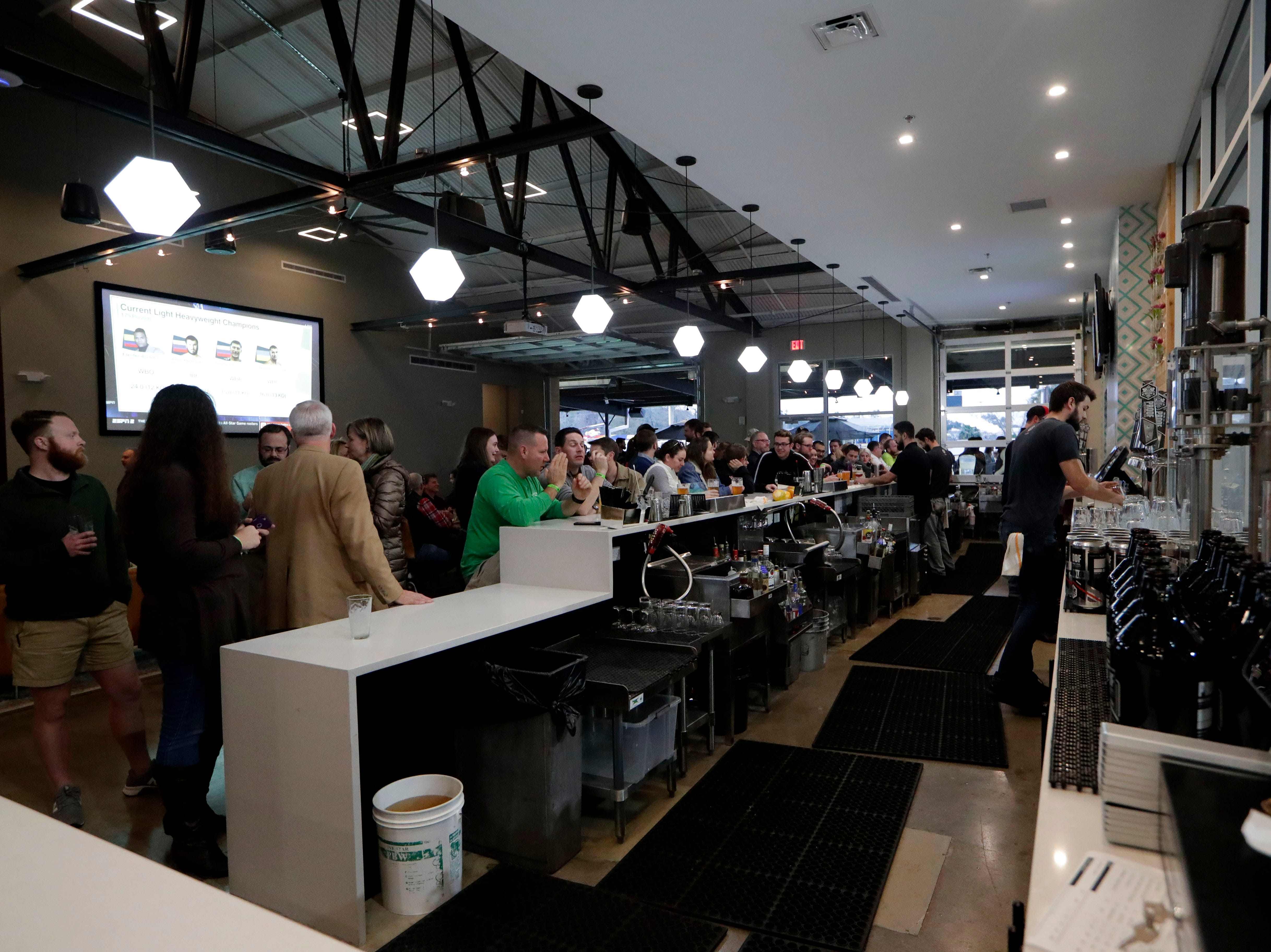 The bar at the new Proof Brewery lined with people chatting and placing drink orders at the soft opening Friday evening, Feb. 1, 2019.