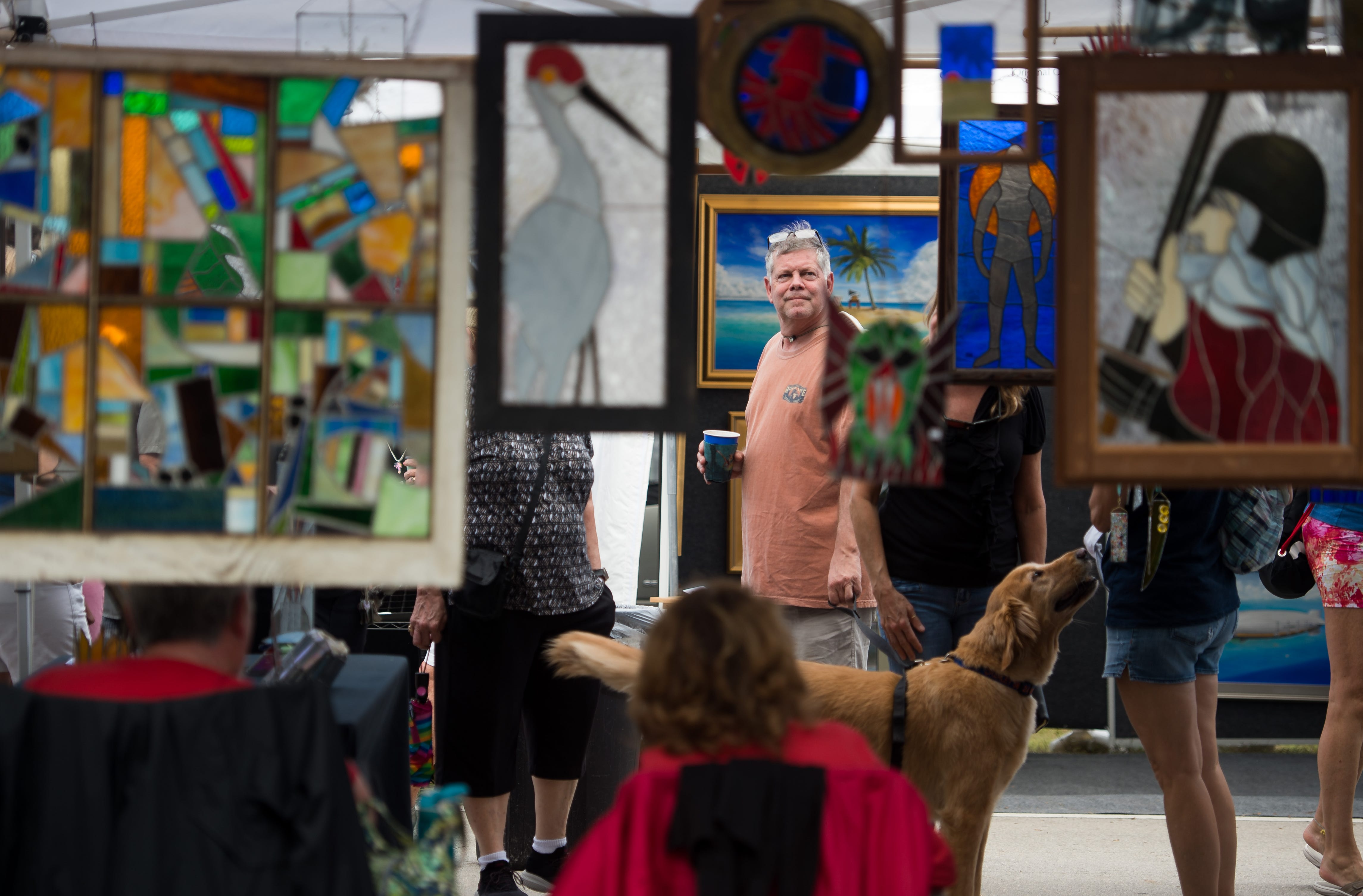 "Scott Meyer (center), of Jupiter, stops with his dog, Charlie, to admire glass artwork by Kenneth Tipping, of Palm Beach Gardens, at the 18th annual Hobe Sound Festival of the Arts along Dixie Highway between Bridge Road and Venus Street on Saturday, Feb. 2, 2019, in Hobe Sound. Meyer, who was attending the event with his wife and friends from Stuart, said, ""Any event that we can walk the streets and drink beer, and take the dog, we go do."" He added they would most likely buy art later. ""I love supporting these hardworking people who come down here…we never leave empty handed."" The free outdoor event, which features artists and craft artisans from around the country, continues from 10 a.m. to 5 p.m. on Sunday."