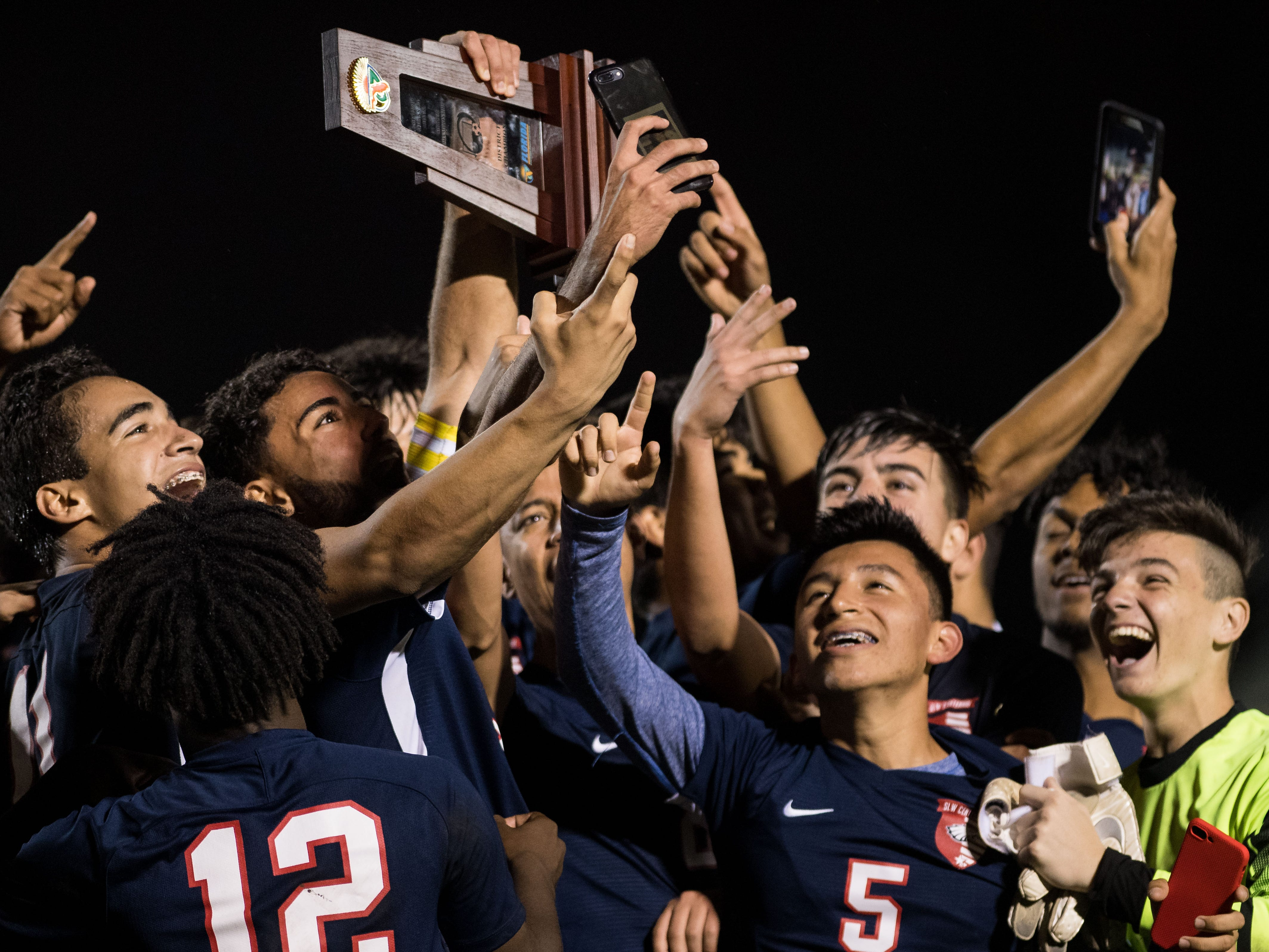 The St. Lucie West Centennial High School varsity boys soccer team celebrates their 3-2 win over Jupiter for the District 10-5A championship title Friday, Feb. 1, 2019, at South County Regional Stadium in Port St. Lucie.