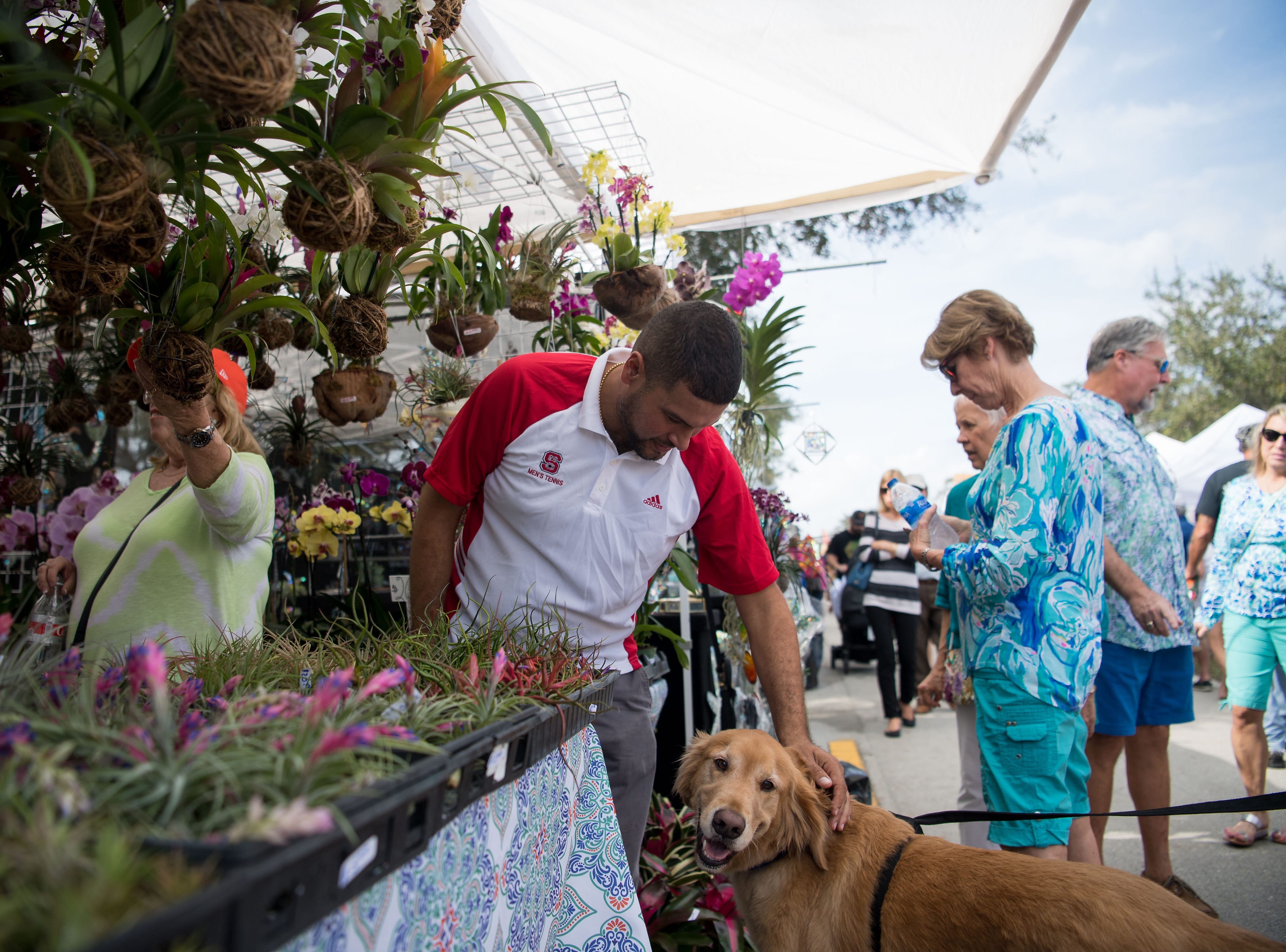 Daniel Hernandez, of Miami, takes a break from tending to orchids and flowers from his nursery to pet Charlie the dog at the 18th annual Hobe Sound Festival of the Arts on Saturday, Feb. 2, 2019, in Hobe Sound.
