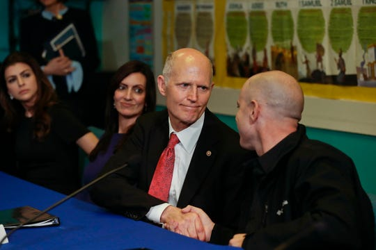 Sen. Rick Scott (center), R-Fla., shakes the hand of Raul Diaz, a Venezuela exile, during a round table discussion on the political crisis in Venezuela on Friday, Feb. 1, 2019, in Doral, Fla.