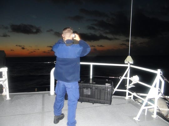 Coast Guard Cutter James (WMSL-754) crewmember stands lookout watch searching for a downed Piper Saratoga aircraft 23 miles of Palm Beach Saturday Feb. 2019. The Coast Guard Cutter Paul Clark (WPC-1106) and Coast Guard Cutter James crews will continue to search during the day. Air Station Miami authorized the launch of a HC-144 to conduct aerial search and rescue efforts.