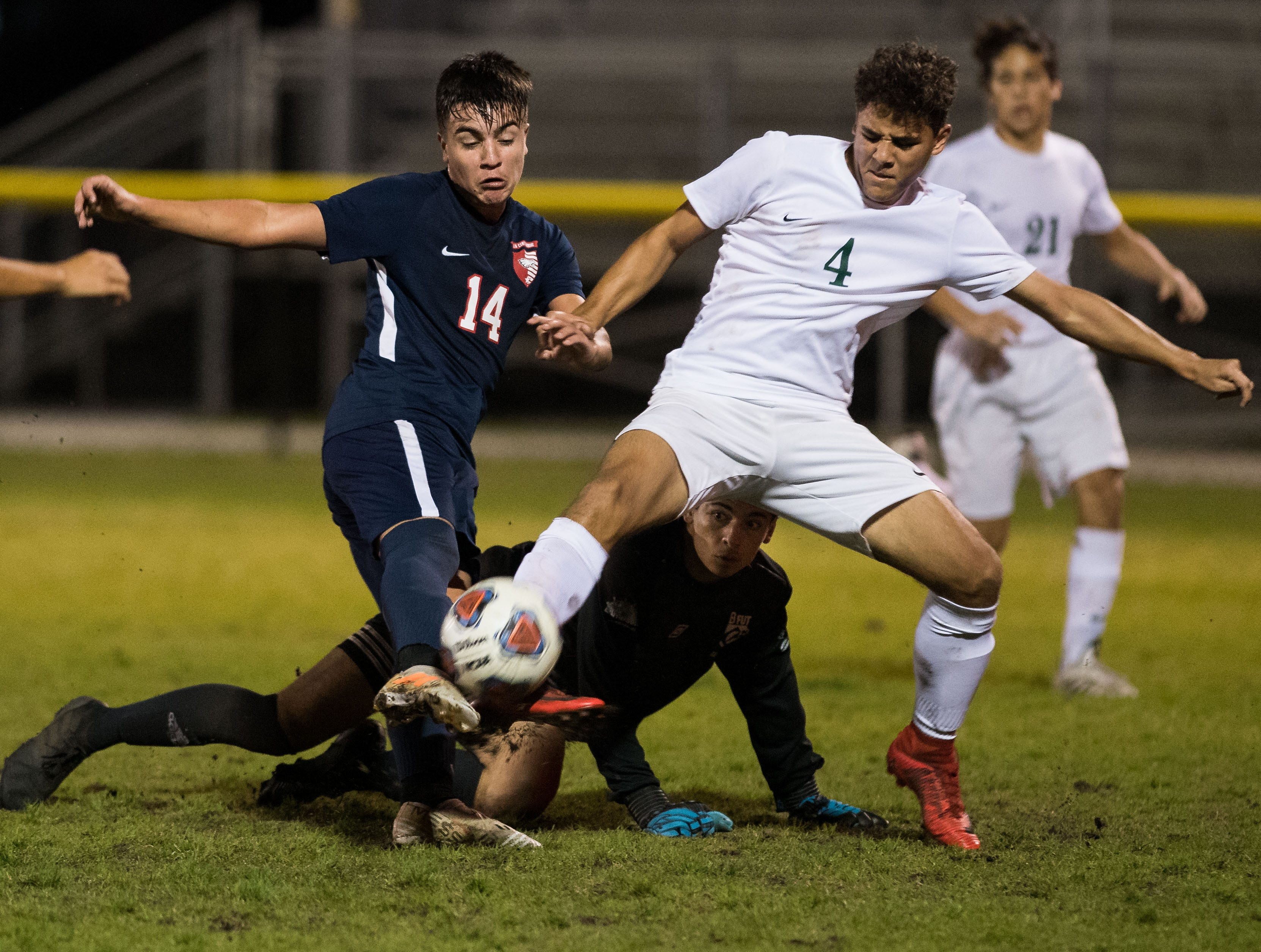 Jupiter's Cory Gonzalez (right) defends against St. Lucie West Centennial's Nico Guerrero, as Jupiter goalkeeper Gil Medina looks on from the ground, during the second half of the high school boys soccer District 10-5A championship game Friday, Feb. 1, 2019, at South County Regional Stadium in Port St. Lucie.