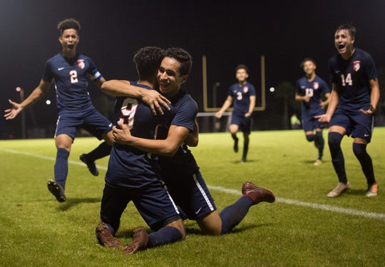 St. Lucie West Centennial's Carlos Rodriguez (center) congratulates teammate Rian Jamai after scoring the game-winning goal with two minutes left against Jupiter during the high school boys soccer District 10-5A championship Friday, Feb. 1, 2019, at South County Regional Stadium in Port St. Lucie. Centennial's Norland Rivera (left) and Nico Guerrero (right) run in for a dog pile.