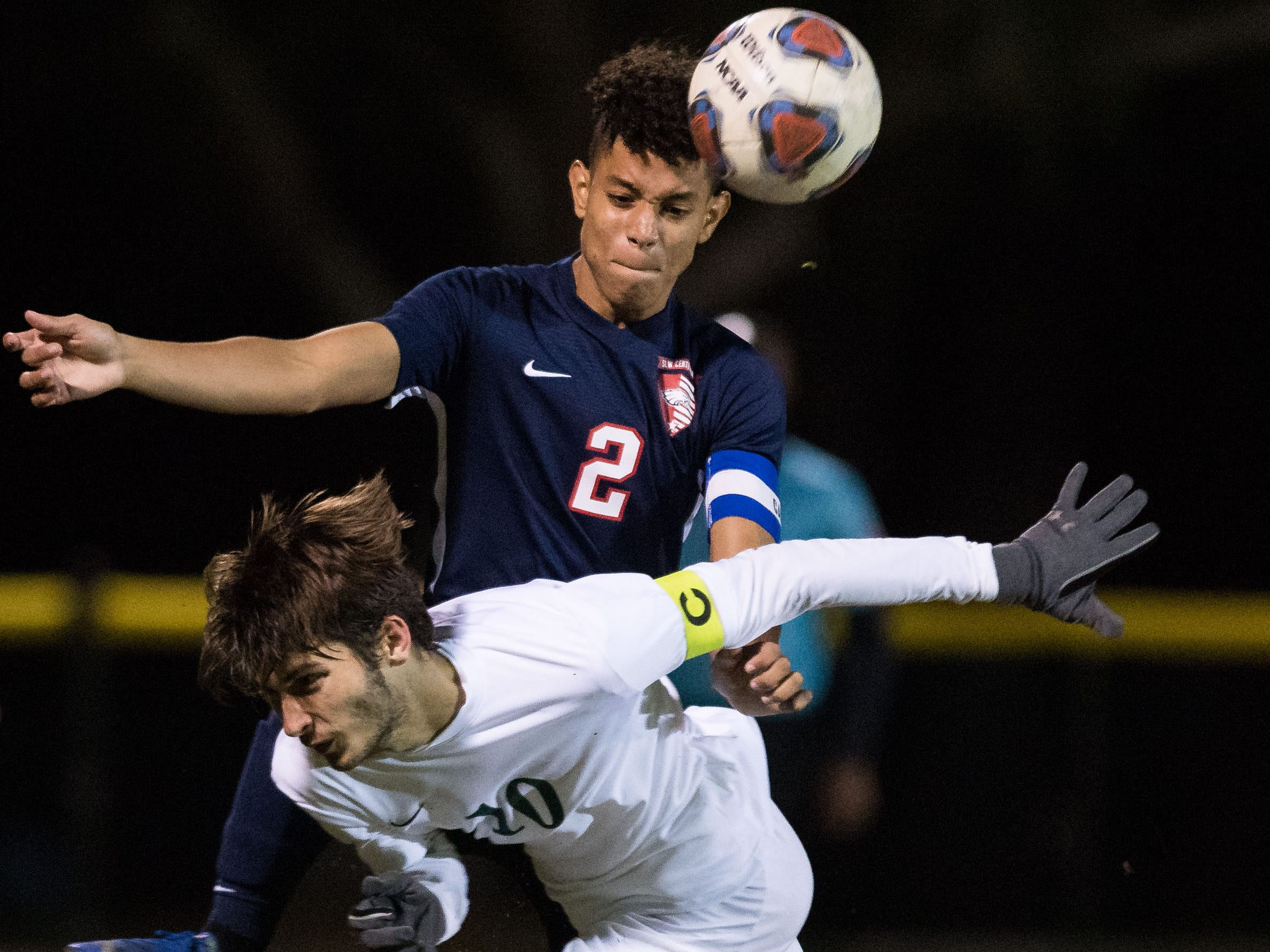St. Lucie West Centennial defender Norland Rivera (top) clears the ball from in front of the goal past Jupiter's Eddie Matot during the second half of the high school boys soccer District 10-5A championship game Friday, Feb. 1, 2019, at South County Regional Stadium in Port St. Lucie.
