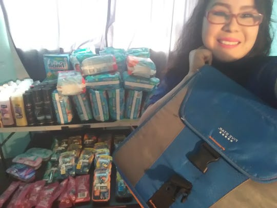 Laura Iracheta Jara holds her coupon binder near her stash of items she's bought with coupons. She has been couponing for six years.