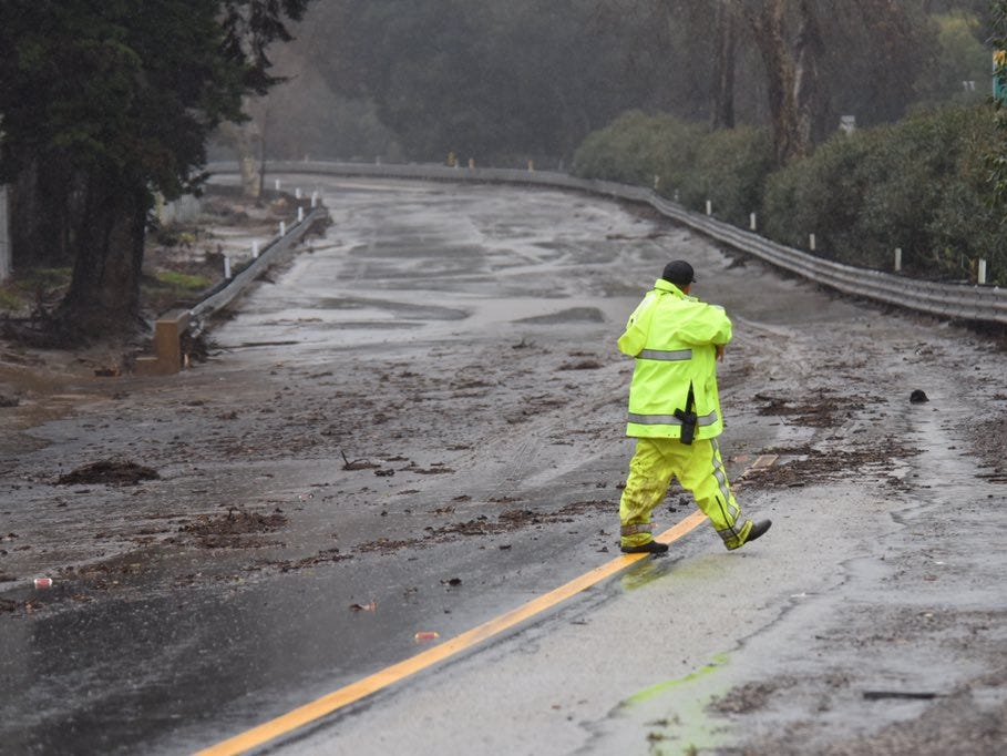 A California Highway Patrol Officer walks on the lanes of northbound Highway 101 in Montecito Saturday morning. Flooding closed the freeway in both directions in the Santa Barbara area as heavy rain pounded the region.