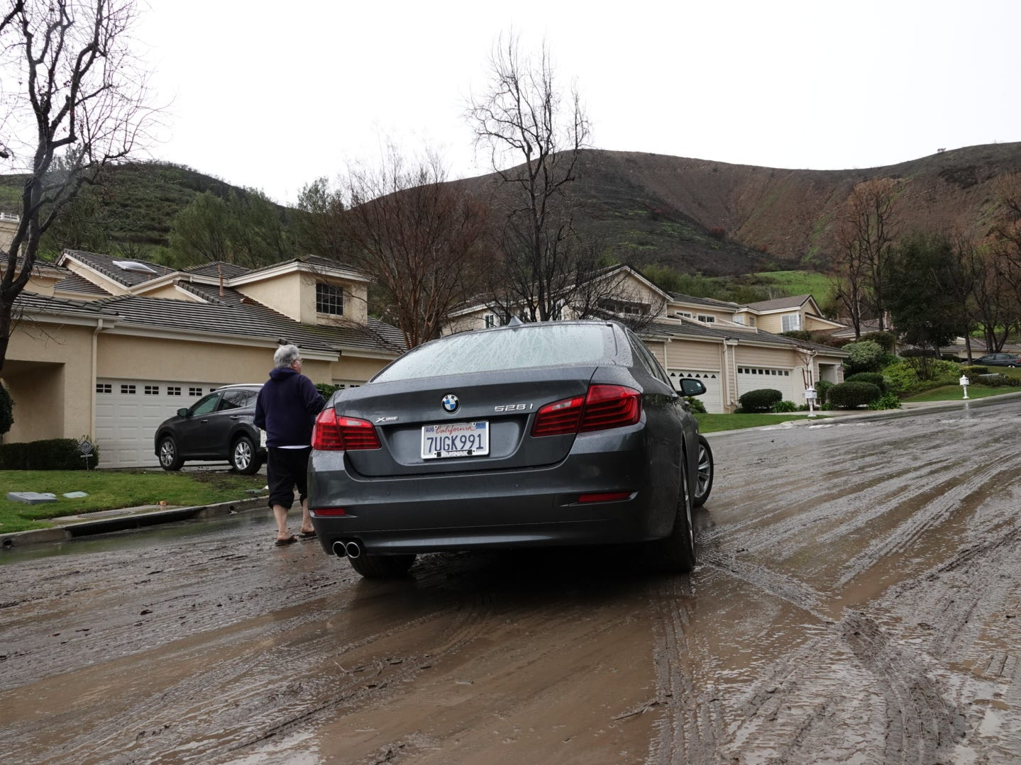 Jerry Lax, on foot, speaks with a neighbor driving through mud Saturday on Westview Court in the Westlake Village area as hills burned by the Woolsey Fire loom behind.