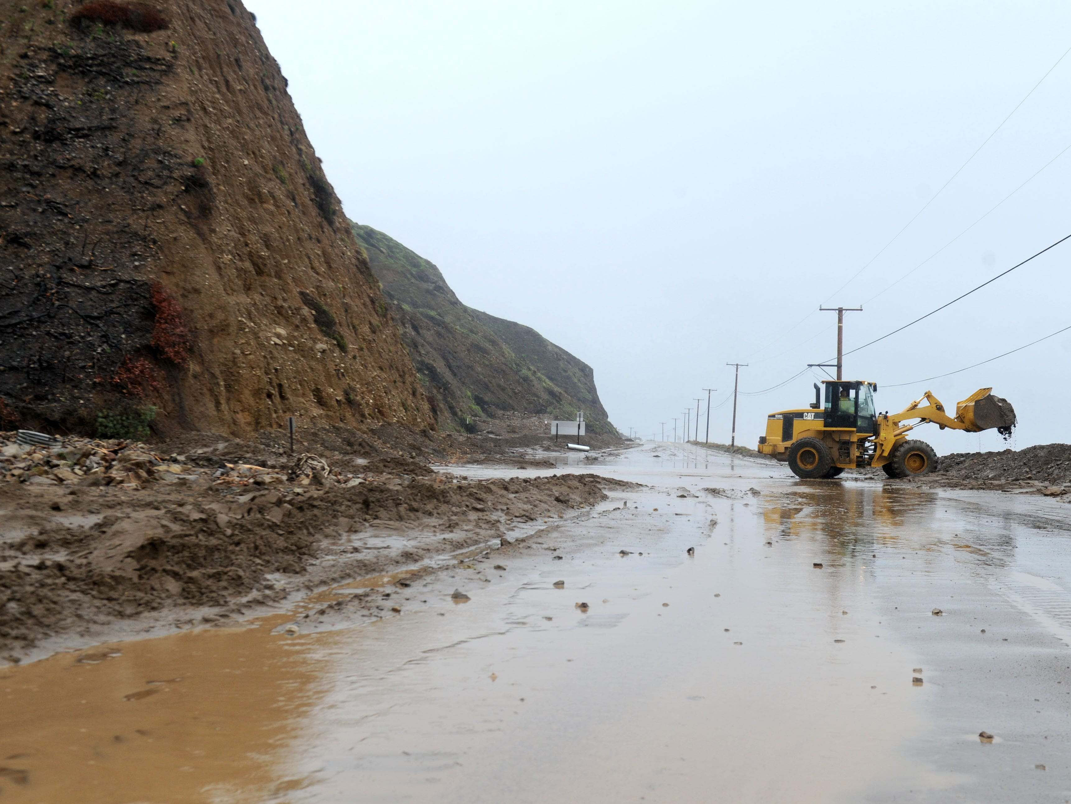 Crews work Saturday to remove dirt and rocks from Pacific Coast Highway near Deer Creek Road after a storm washed debris onto the thoroughfare.