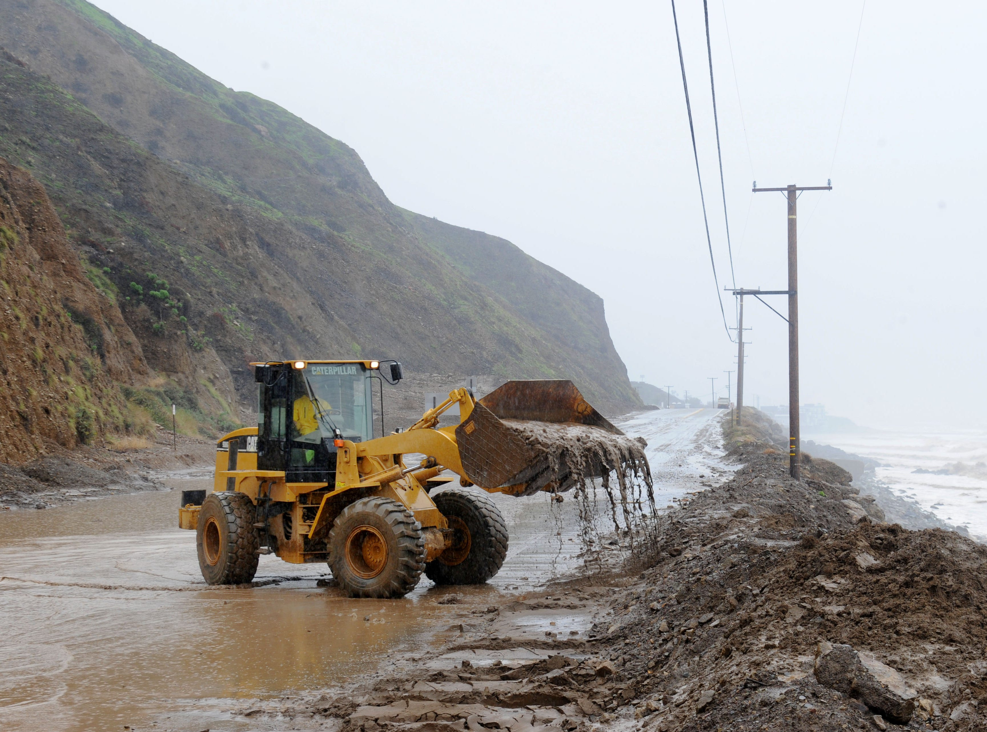 Crews work to remove dirt and rocks from Pacific Coast Highway near Deer Creek Road on Saturday after a storm moved through.