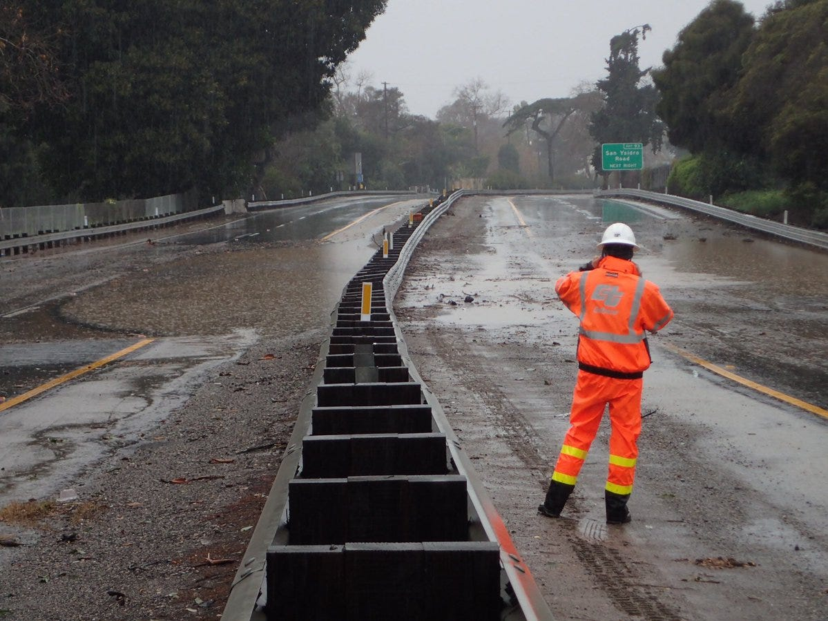 A Caltrans worker on Highway 101 in Montecito Saturday morning after flooding closed the freeway in both directions.