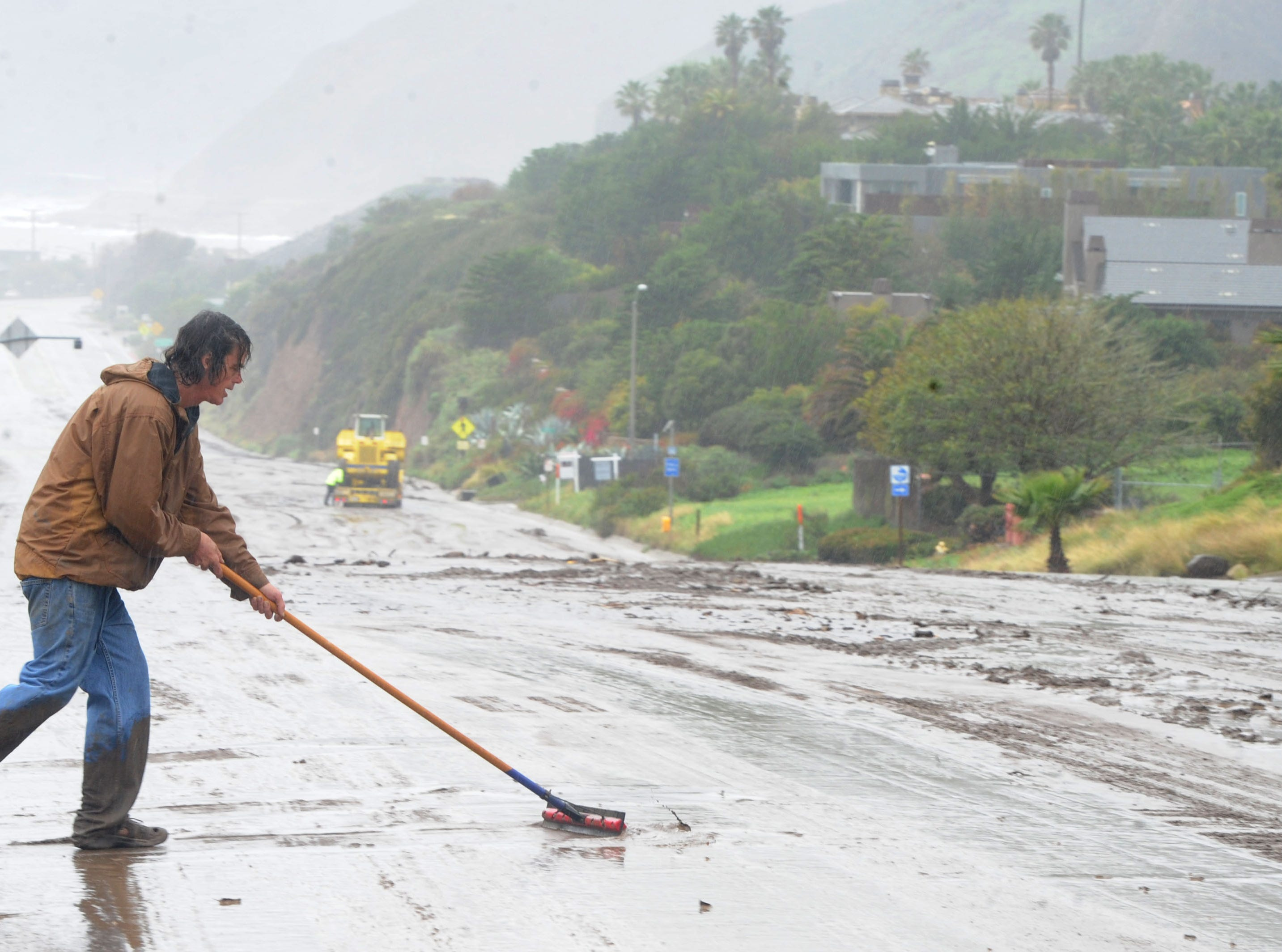 Bud Robison, employed by the Malibu Bay Club, cleans mud from the entrance along Pacific Coast Highway on Saturday after a storm moved through.