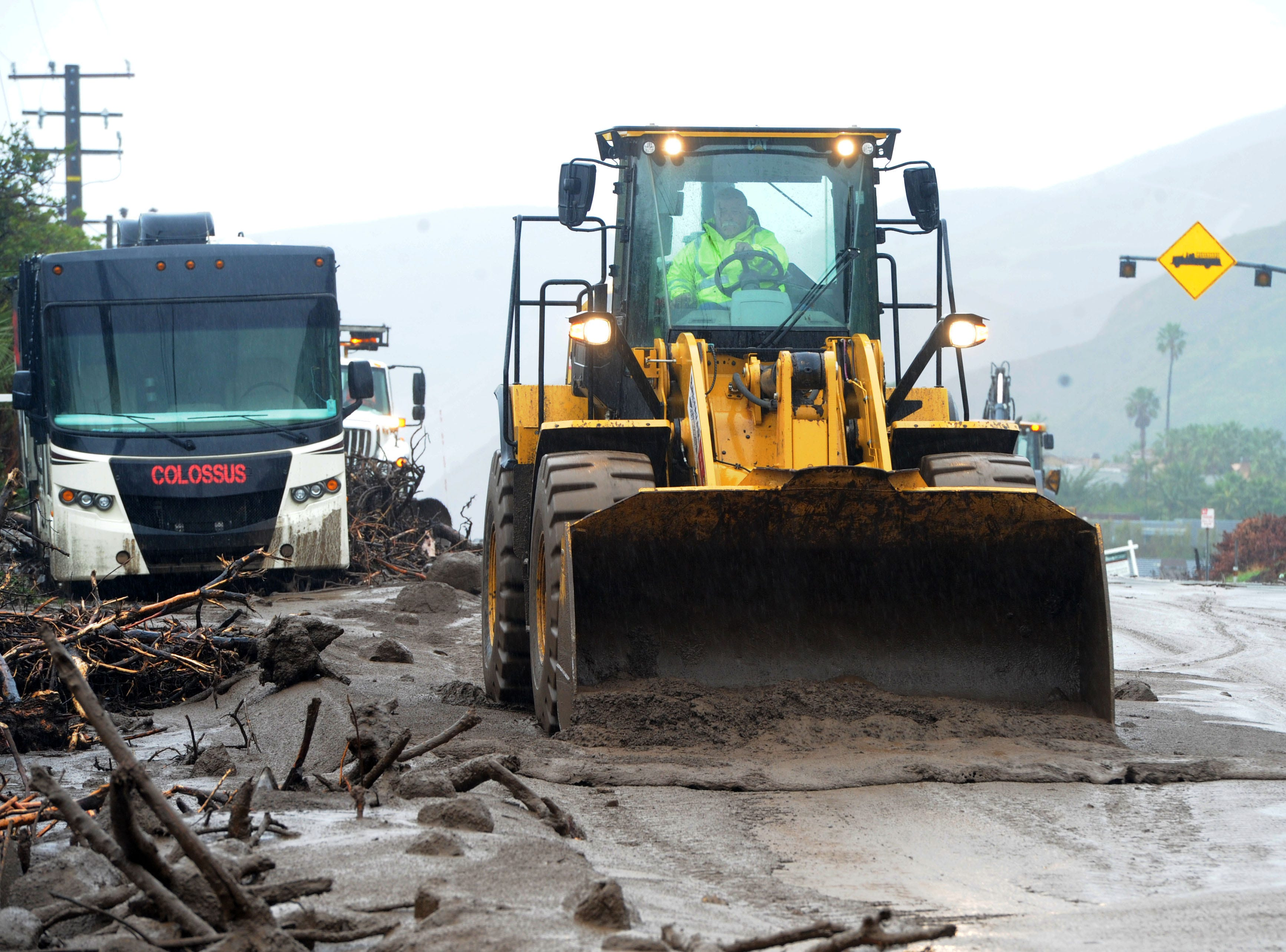 Crews work to remove dirt and rocks from Pacific Coast Highway between Point Mugu and Malibu on Saturday after a storm moved through. The debris led to the highway's closure.