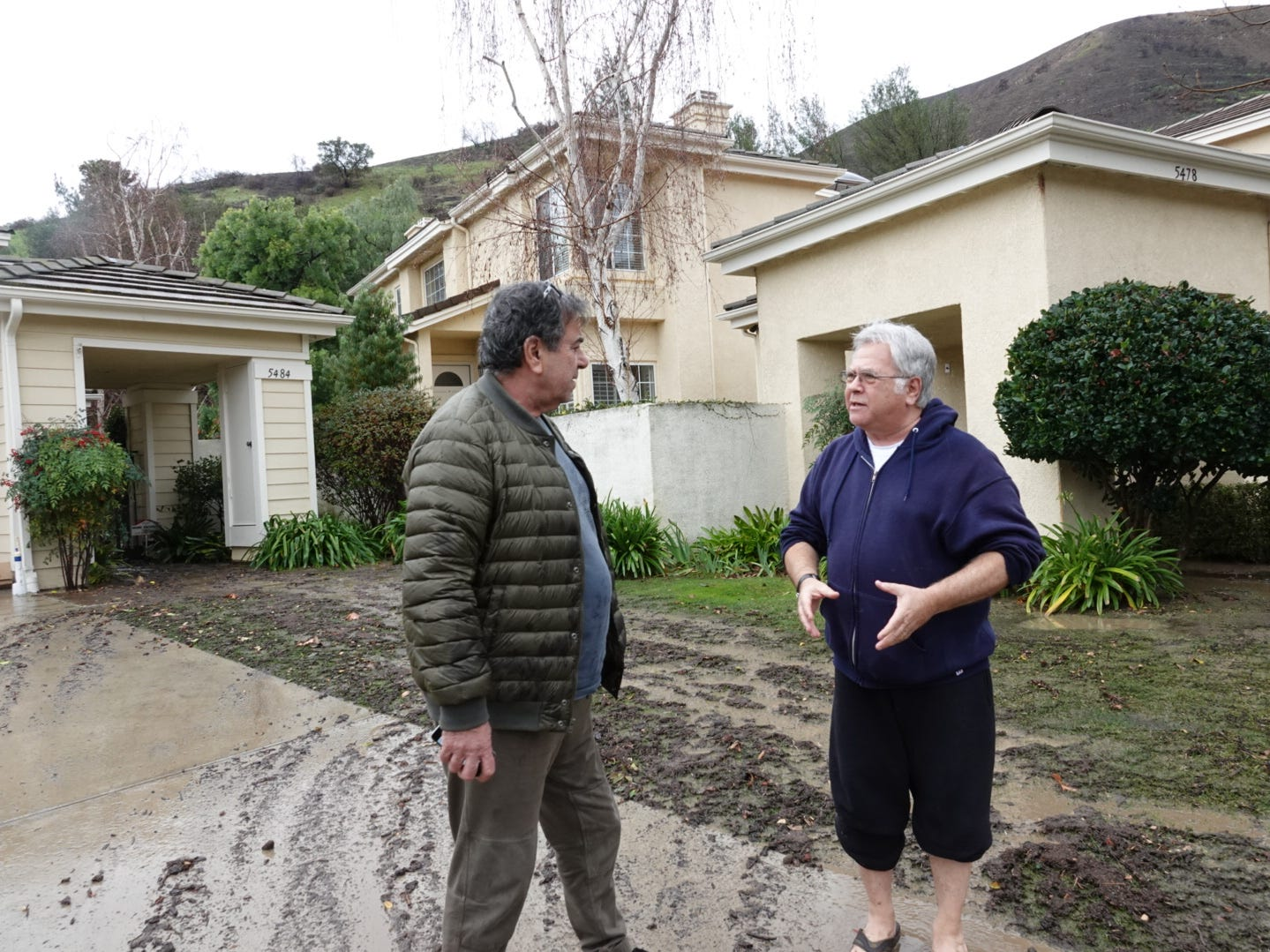 Neighbors Panos Sklavenitis, left, and Jerry Lax discuss mud impacting their homes on Saturday after a major storm moved through the Ventura County region.