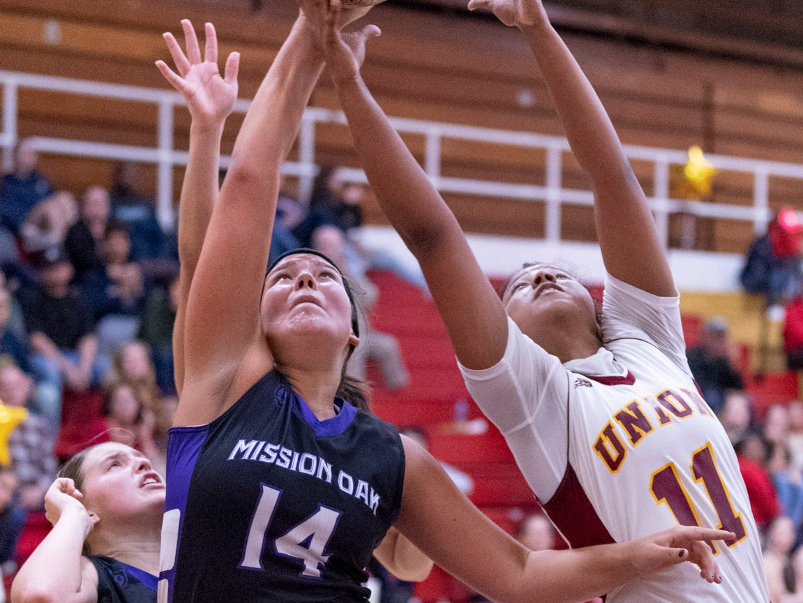 Tulare Union's Kiara Brown, right, and Mission Oak's Kayleigh Lopes go up for a rebound in a girls basketball game on Friday, February 1, 2019.