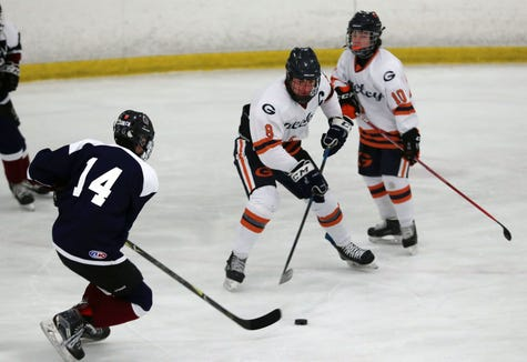 Rye Town/Harrison's Jack Shapiro (14) tries to get around Greeley's Liam Whitehouse (8) during hockey action at the Brewster Ice Arena Feb. 1,  2019.