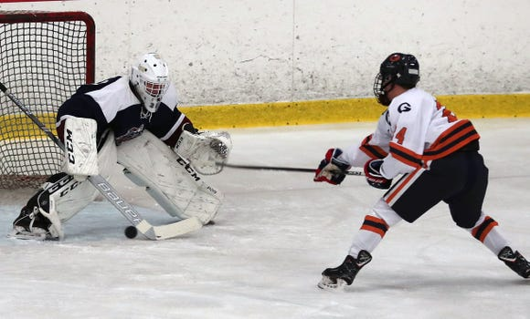 Rye Town/Harrison goalie Barry Nico stops a shot from Greeley's Ryan Renzulli (24)  during hockey action at the Brewster Ice Arena Feb. 1,  2019.