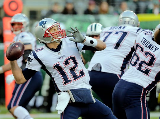 FILE - In this Nov. 25, 2018, file photo, New England Patriots quarterback Tom Brady (12) throws a pass as his offensive line blocks during the second half of an NFL football game against the New York Jets in East Rutherford, N.J. They're big boys with mean streaks and nasty attitudes on the field, yet the Patriots' offensive line still gets somewhat overlooked at times. During the playoffs, they've been as big a key as any position group by keeping Tom Brady clean and clearing the way for the running game. (AP Photo/Seth Wenig, File)