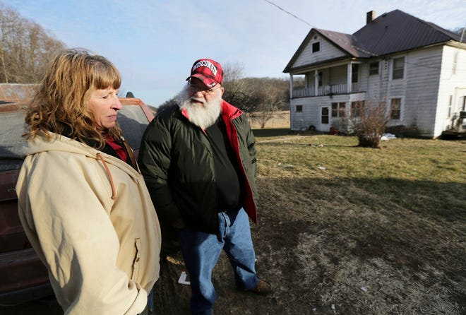 Julie and Phil Henneman, who lost their son Keith to suicide in 2006, when he was 29, talk about the experience outside the old farmhouse in Boscobel, Wis. The Hennemans continue to live on the 215-acre farm with two other sons, but they aren't farming.