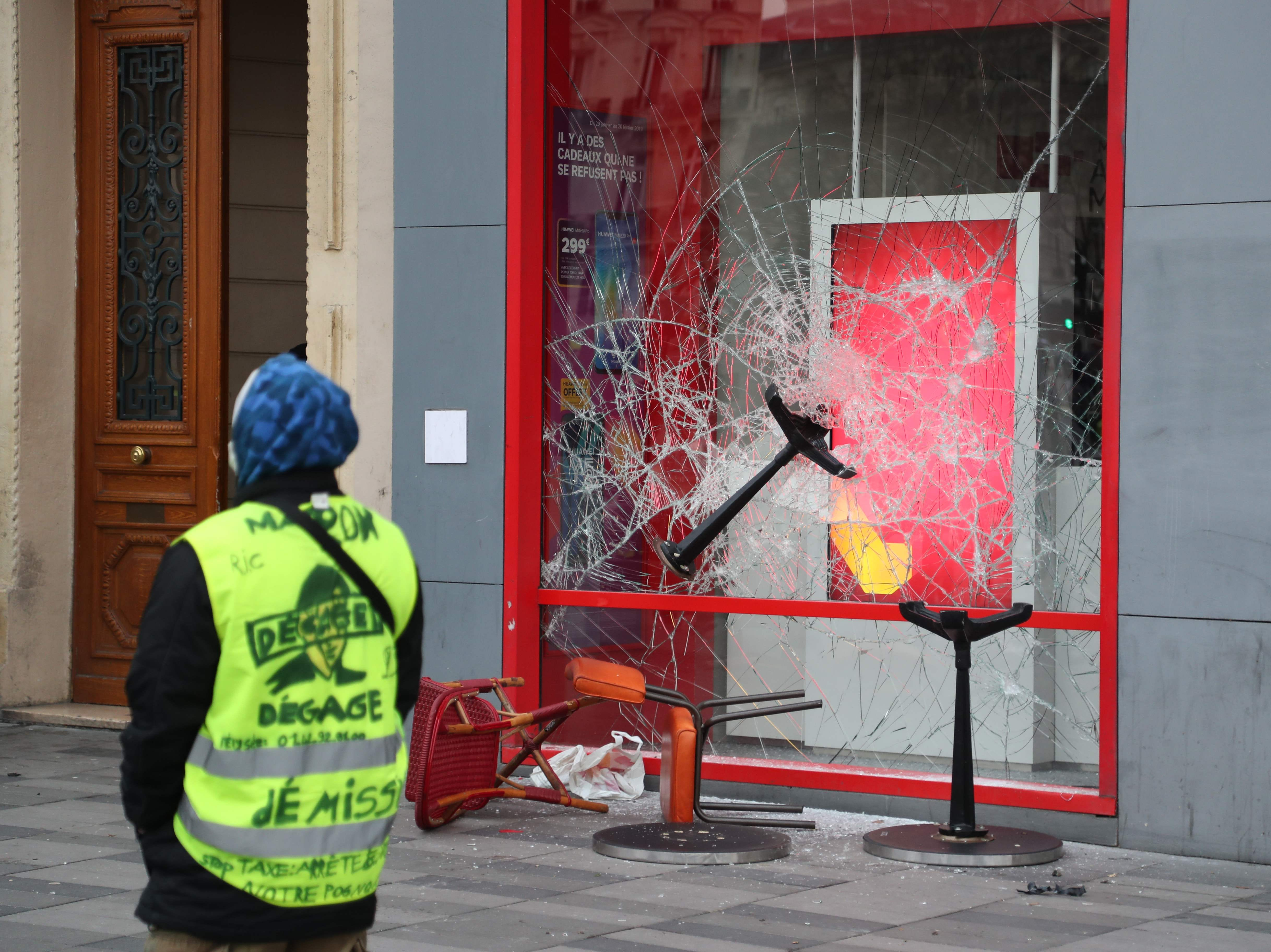 A protester walks past a vandalized shop window during clashes with police at Place de la Republique on Feb. 2, 2019 in Paris, on the sidelines of a march called to pacifically protest against police violence toward participants of the last three months demonstrations in France, as yellow vest protesters take to the streets for the 12th consecutive Saturday.
