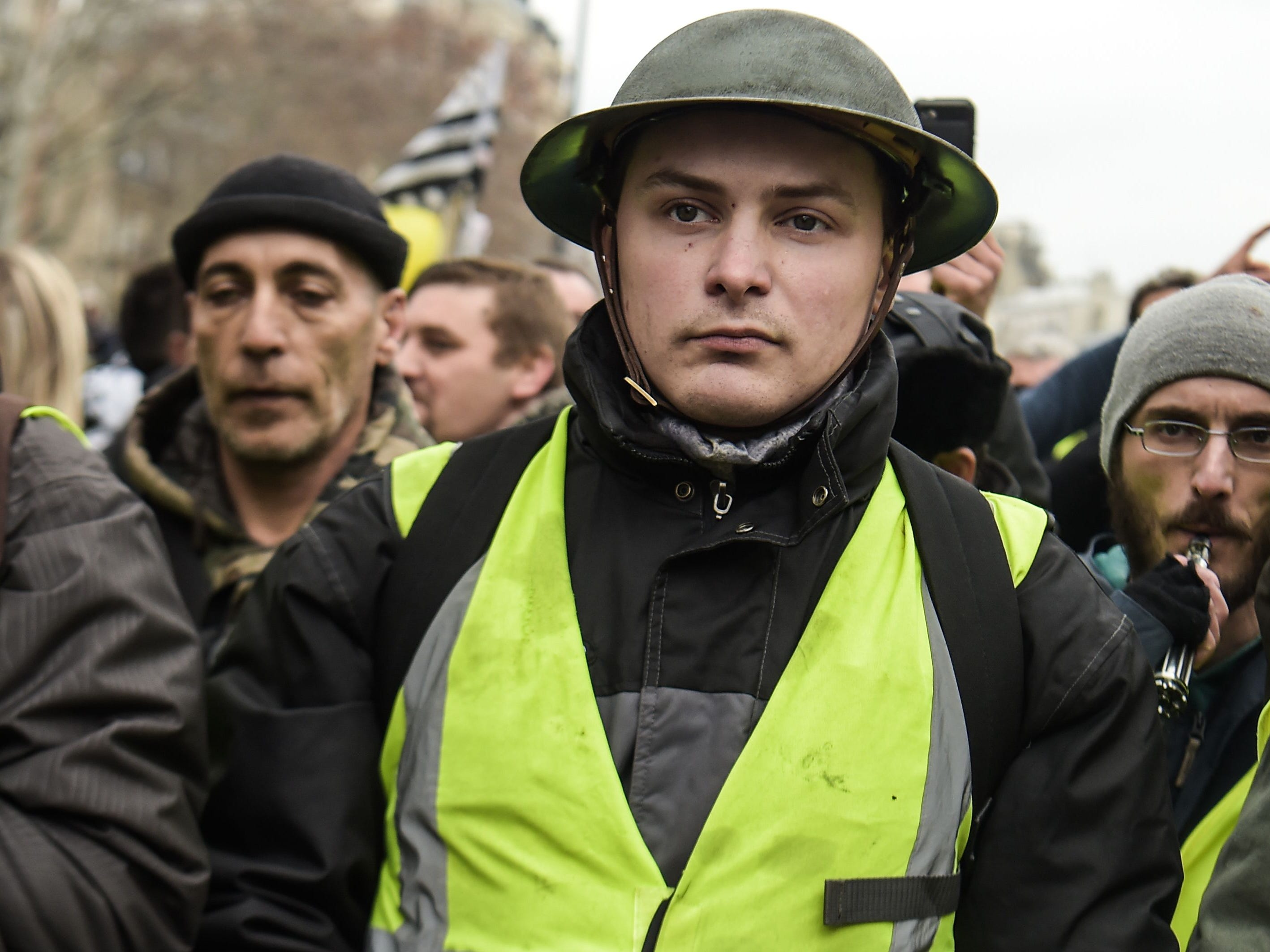 A man wearing a vintage army helmet takes part in a march on Feb. 2, 2019 in Paris, called to pacifically protest against police violence toward participants of the last three months demonstrations in France, as Yellow Vest protesters take to the streets for the 12th consecutive Saturday.