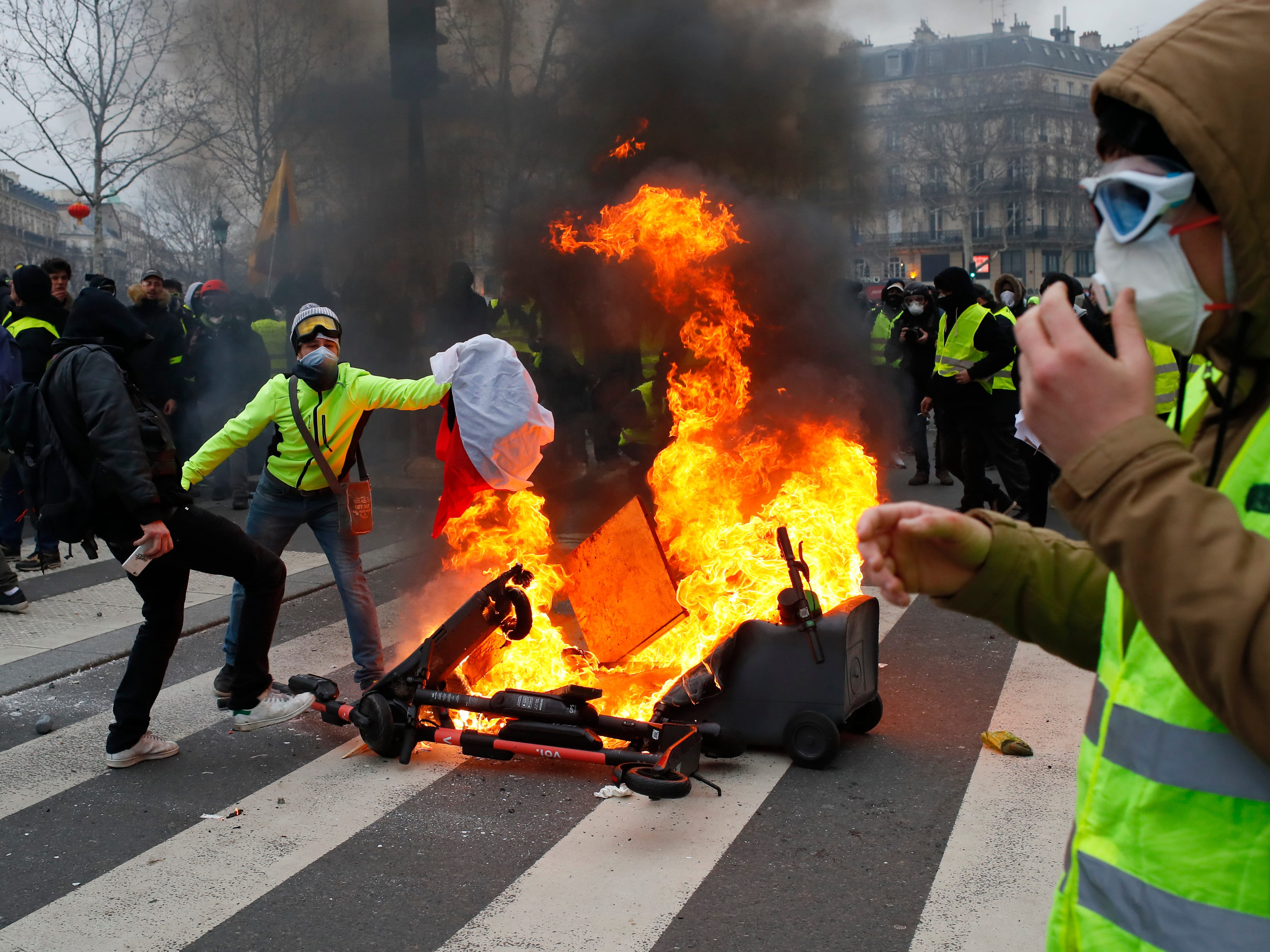 Demonstrators set a fire on the Place de la Republique after a yellow vest protest, Saturday, Feb. 2, 2019 in Paris. France's yellow vest protesters were back on the streets Saturday to keep pressure on French President Emmanuel Macron's government and denounce the large number of people injured in demonstrations they say is the result of police violence.