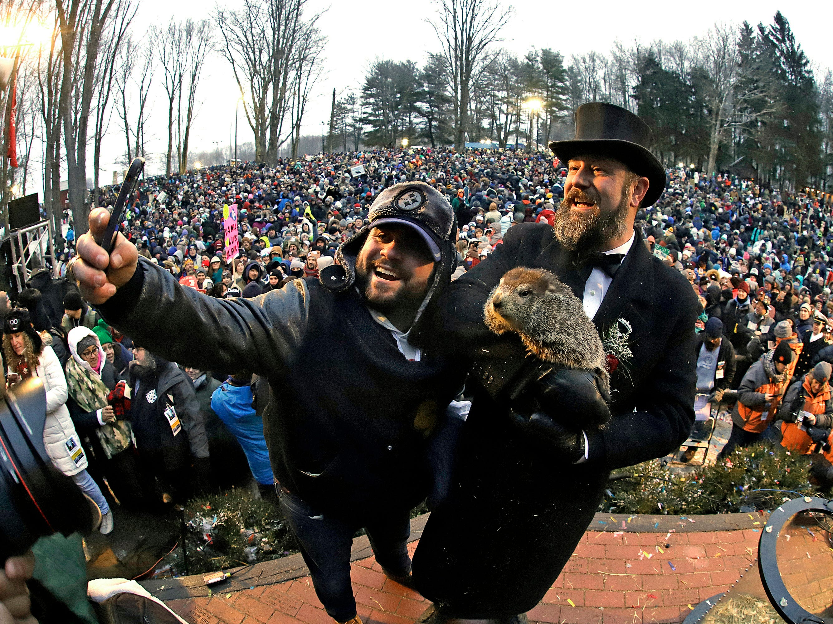 Groundhog Club co-handler Al Dereume, right, holds Punxsutawney Phil, the weather prognosticating groundhog, and poses for a selfie with a groundhog fan.