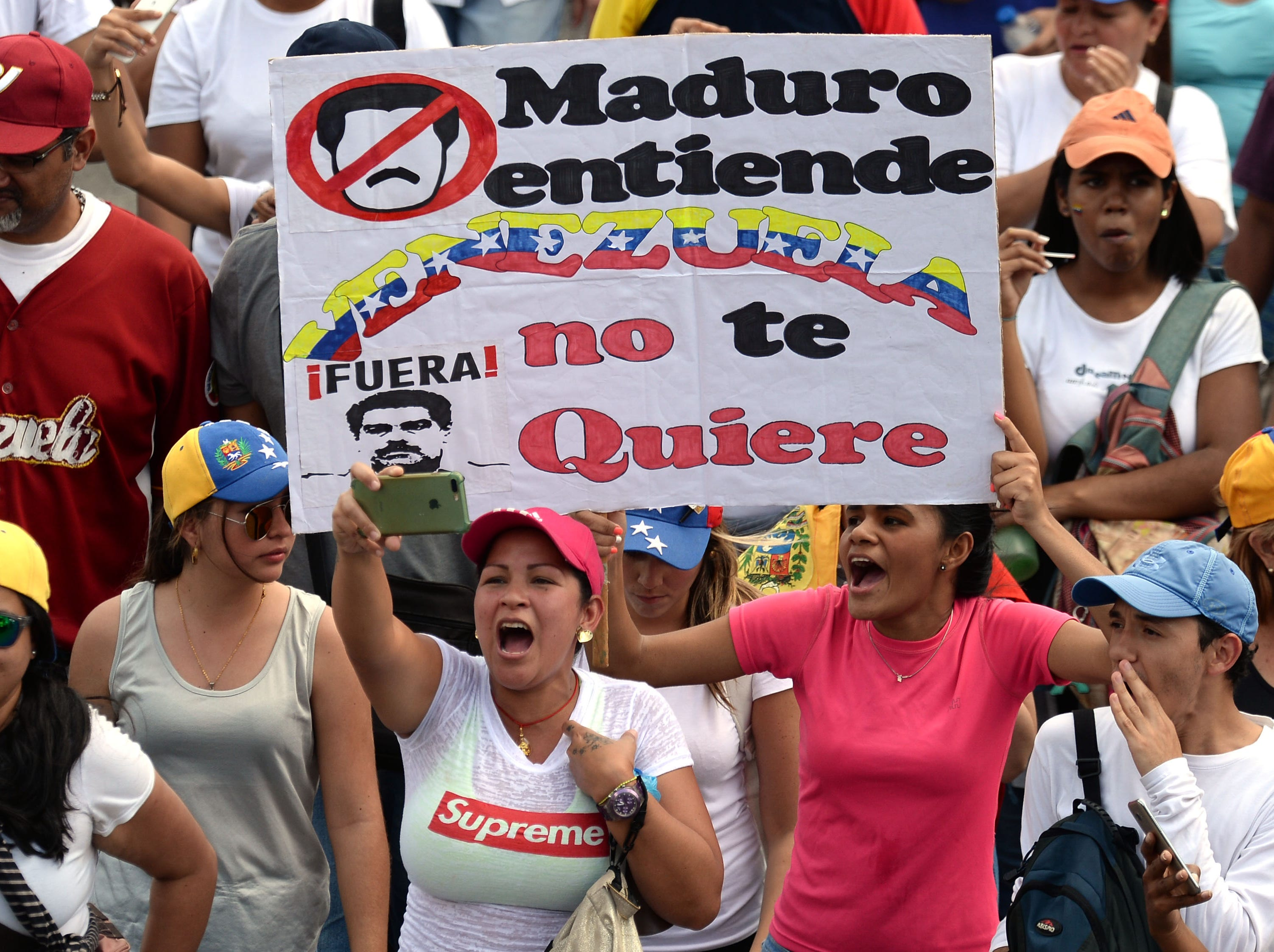 "An opposition supporter holds a placard reading ""Maduro, Understand: Venezuela Doesn't Want You"" during a gathering with Venezuelan opposition leader Juan Guaido, in Caracas on Feb. 2, 2019.  Tens of thousands of protesters were set to pour onto the streets of Caracas to back self-proclaimed acting president Guaido's calls for early elections as international pressure increased on President Nicolas Maduro to step down. Major European countries have set a Sunday deadline for Maduro to call snap presidential elections."